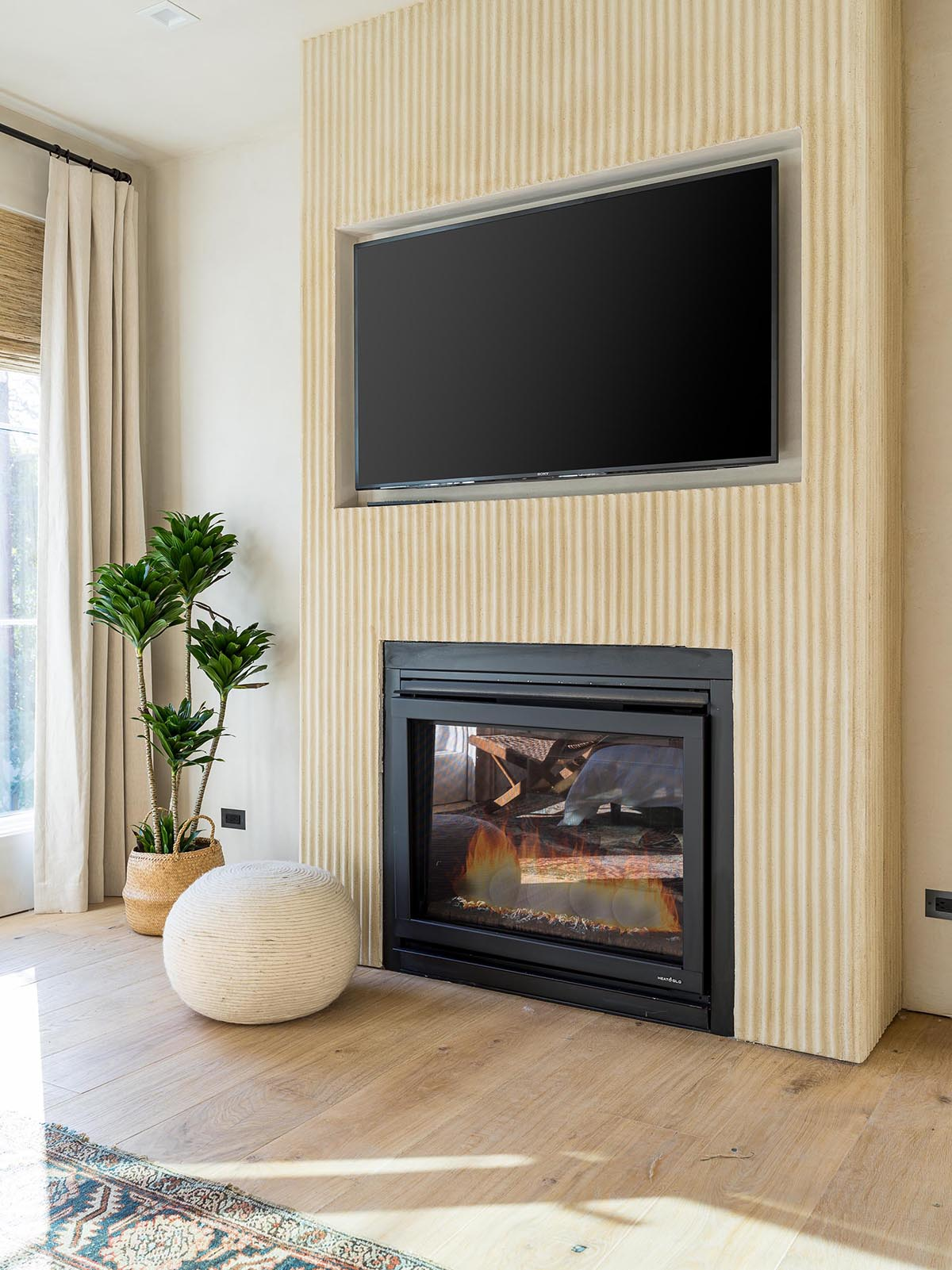 The primary bedroom has textured accents walls, as well as a fireplace and recessed television.