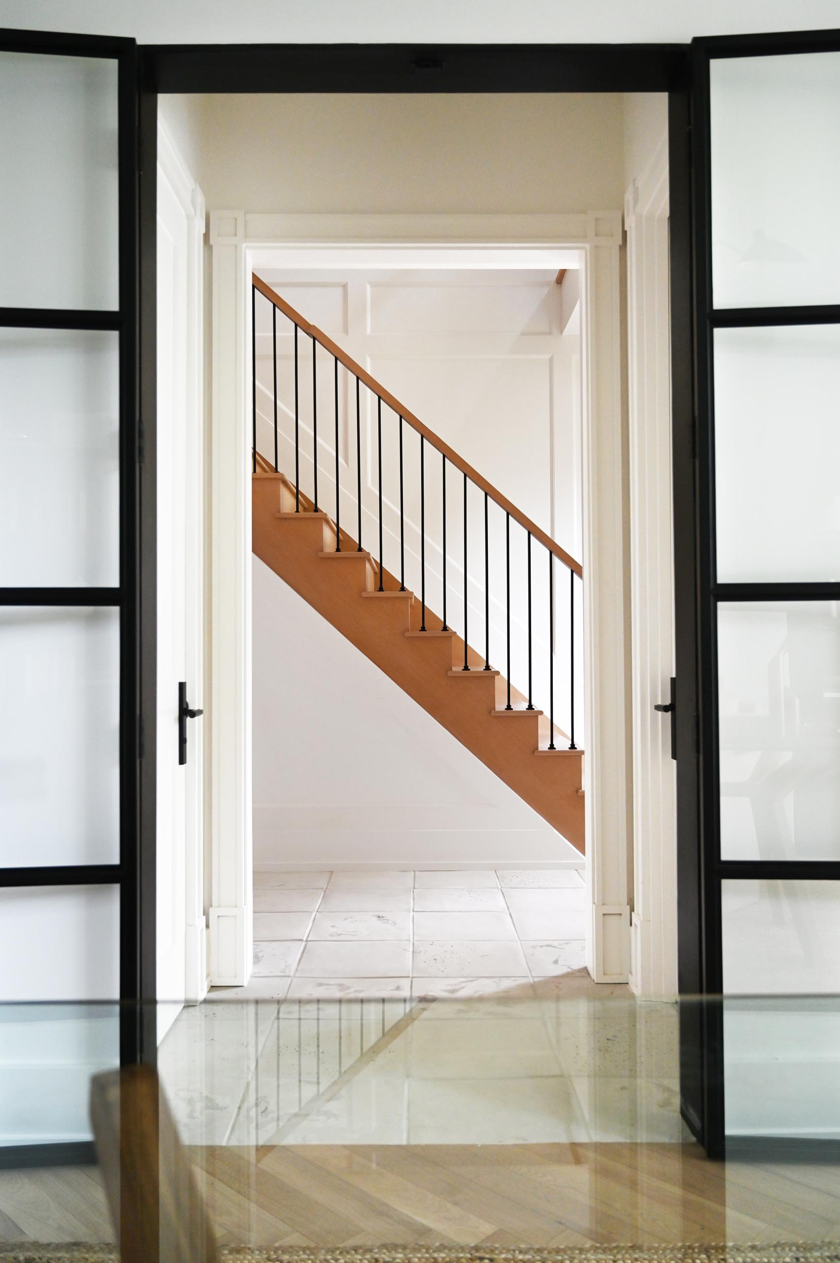 Black metal stair pickets and feature wall paneling, lead up to the second floor, where one is met with a catwalk overlooking the dining and kitchen space below.