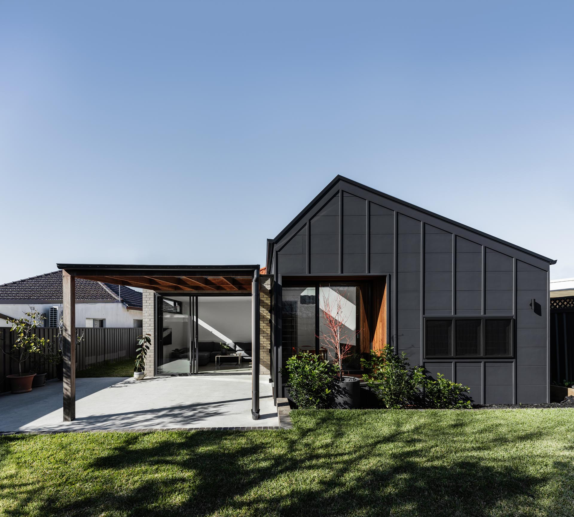 A simplified rear addition with a black and brick exterior includes a kitchen, dining, and living room with an improved connection to the outdoors via a covered patio.