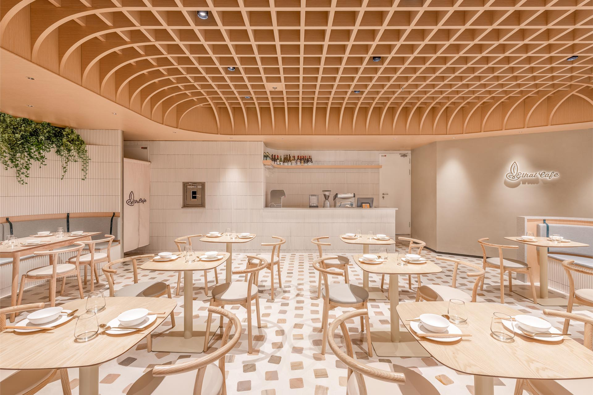 A modern cafe with a design that includes a dome-shaped ceiling, formed by a grid of wooden beams, in which conceals the space's lighting.
