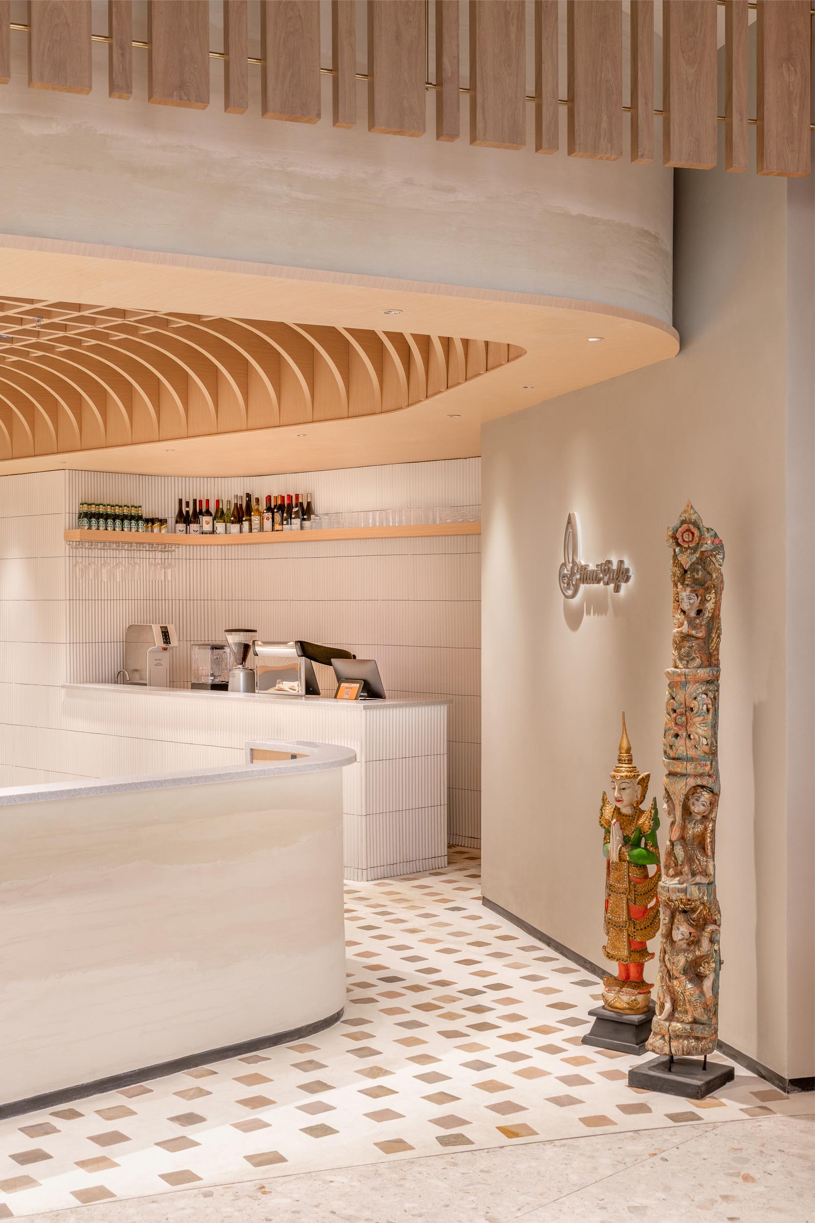 The nooks and sitting areas of this modern cafe appear to have been carved out of the rammed earth that envelops the facade.