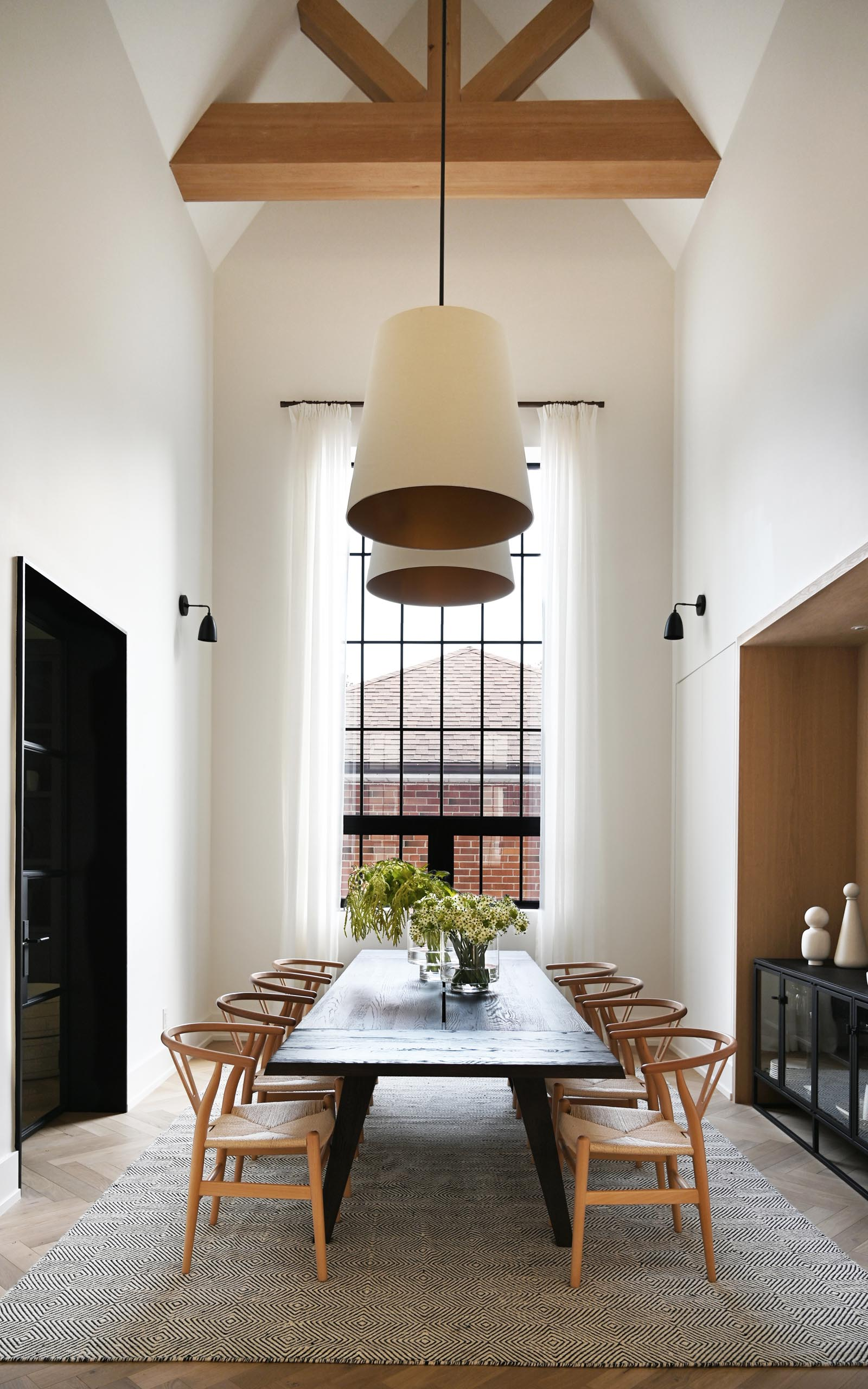 This farmhouse-inspired kitchen and dining room feature cathedral ceilings with exposed wood beams, warm wood accents and natural materials. Oversized pendant lights complement the grand space, and add a warm glow for evenings spent around the large dining table.
