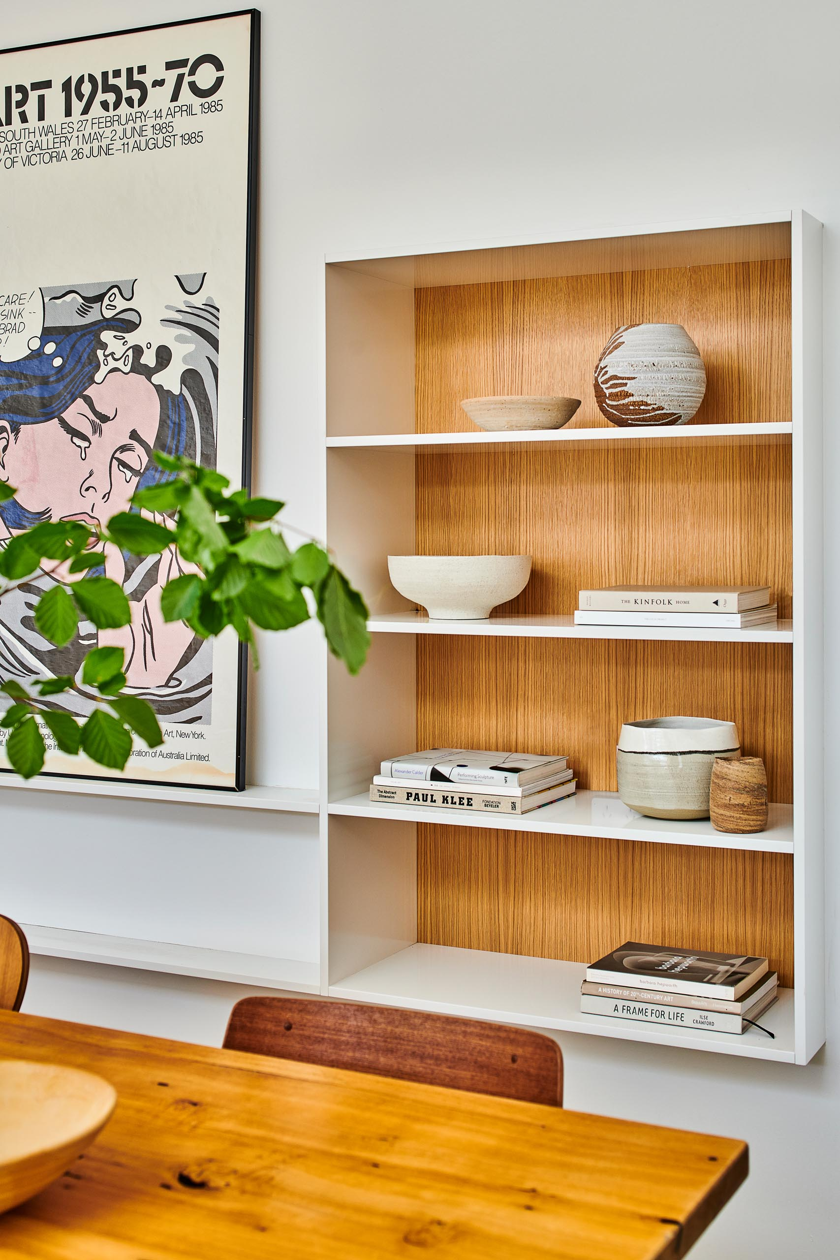 In this modern dining area, there's a bookshelf that's partially set back into the wall. The wood backing allows the decorative items to stand out.