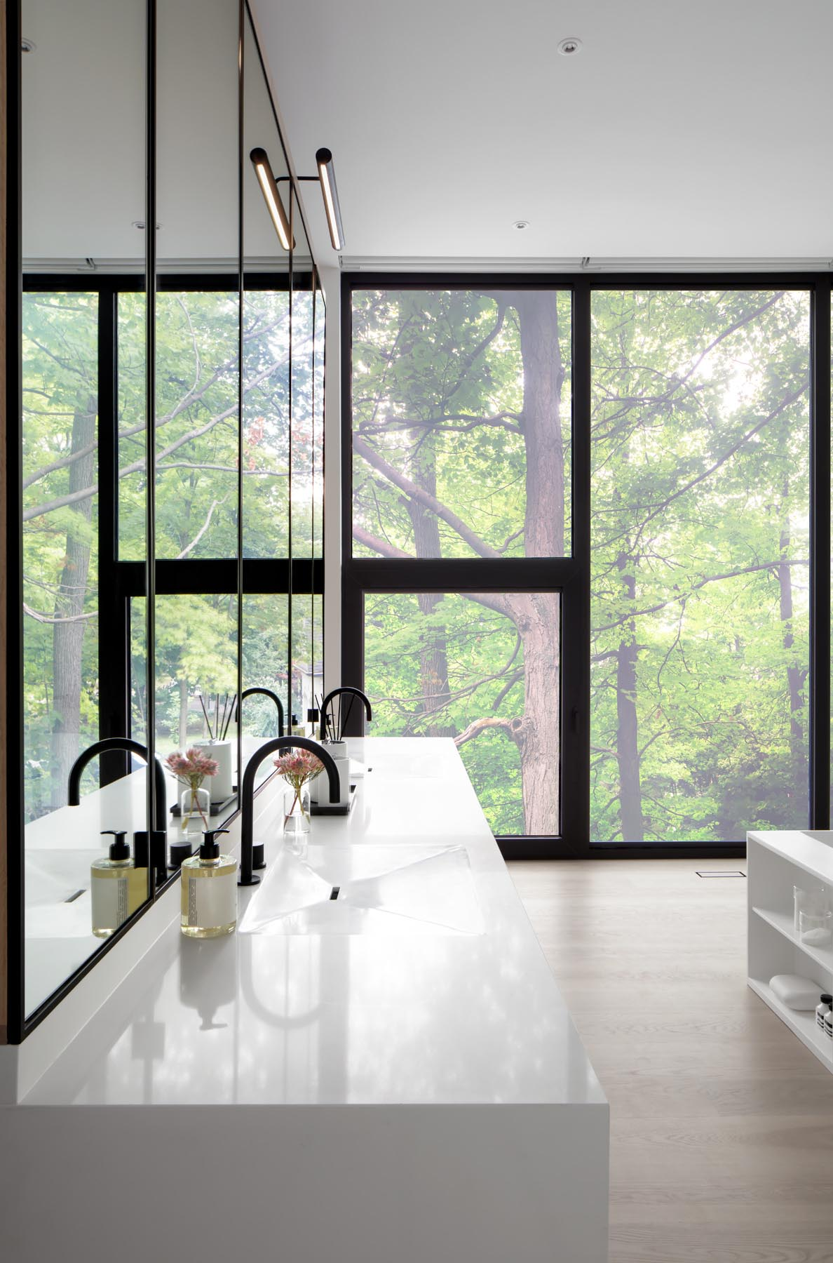 A wall of wood closets link the bedroom to this modern en-suite bathroom, that showcases a white vanity with large mirrors, a built-in bathtub, and a double shower with glass surround.