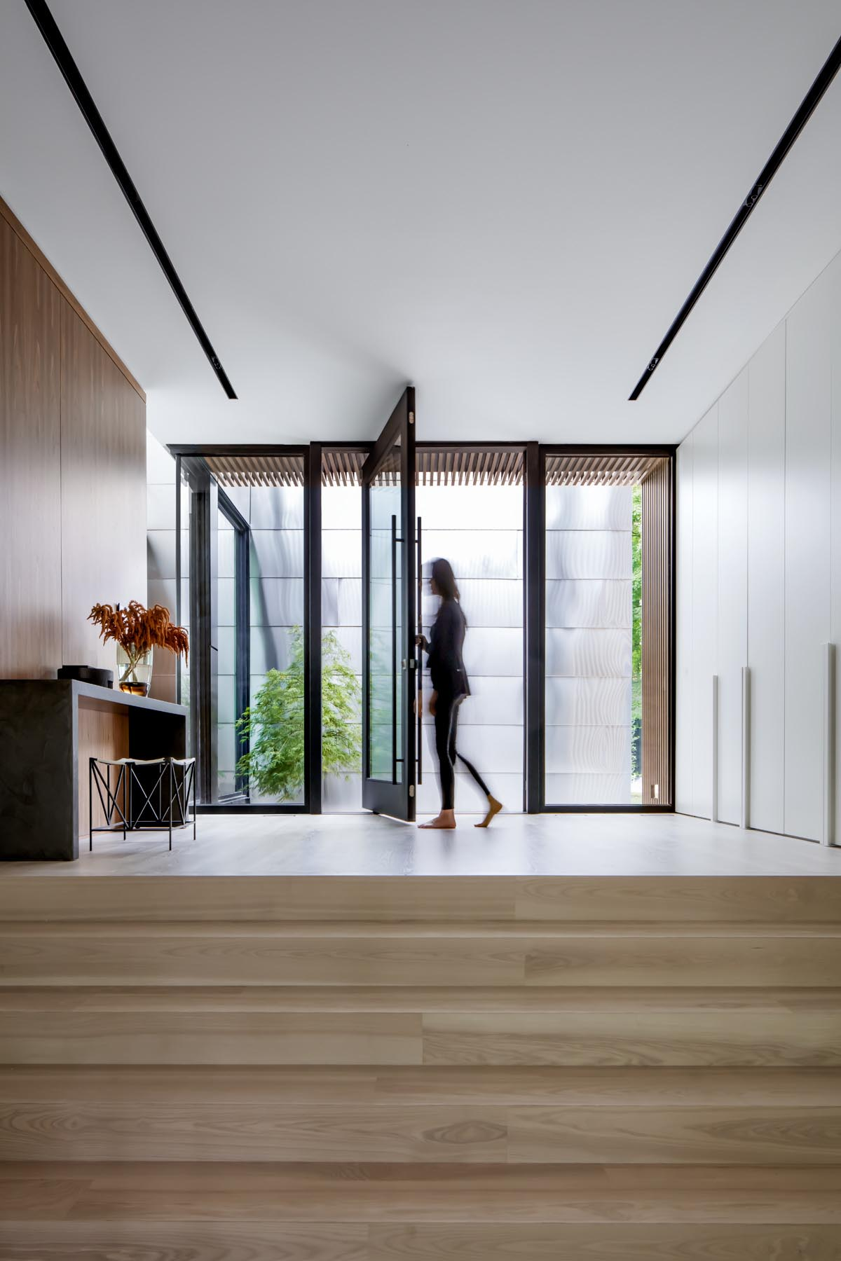 Welcoming visitors to this modern home is a 7-foot wide black-framed glass pivot door, that opens into the entryway furnished with a console table and a stool.