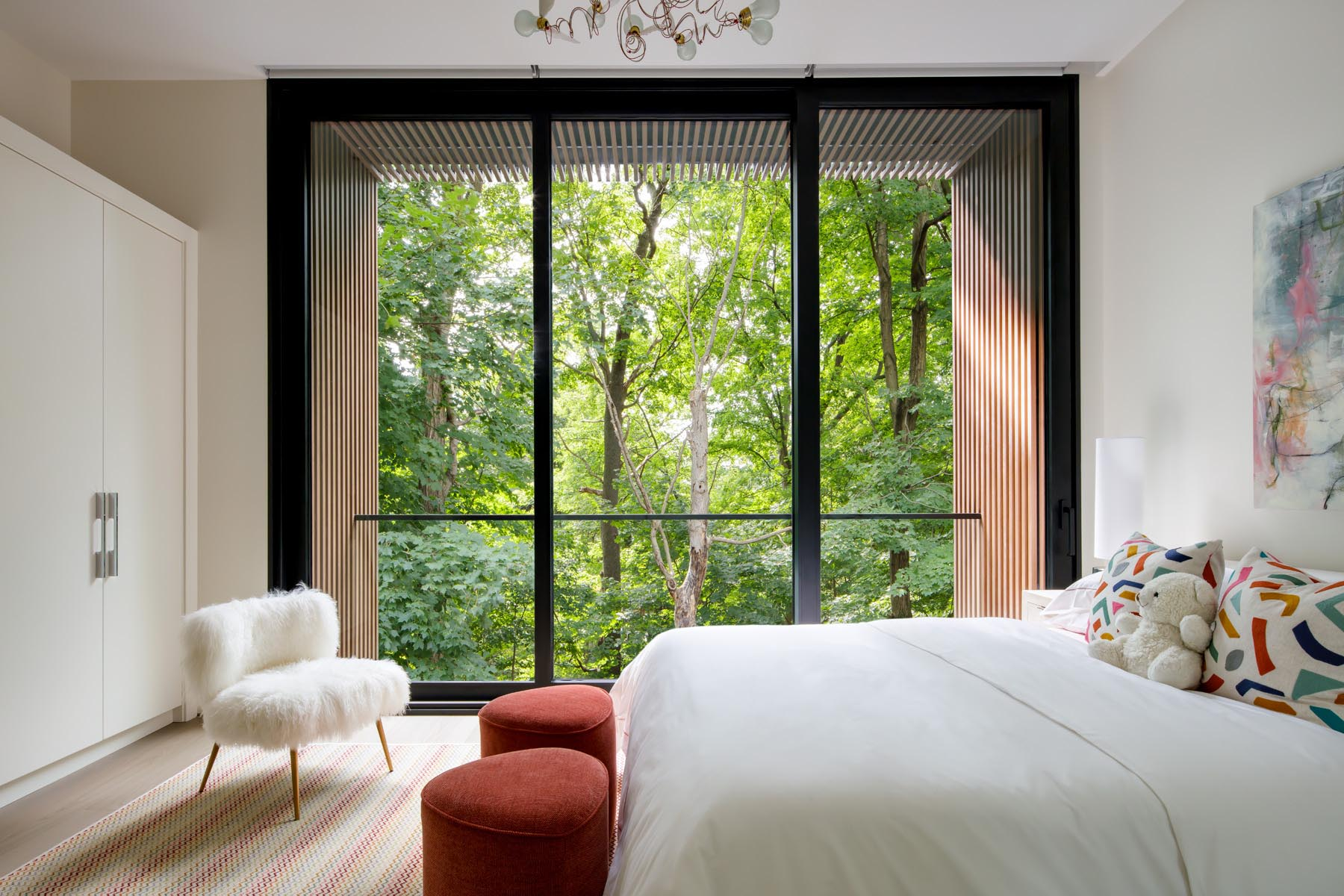 A modern bedroom with a glass door that opens to a small balcony with tree views.