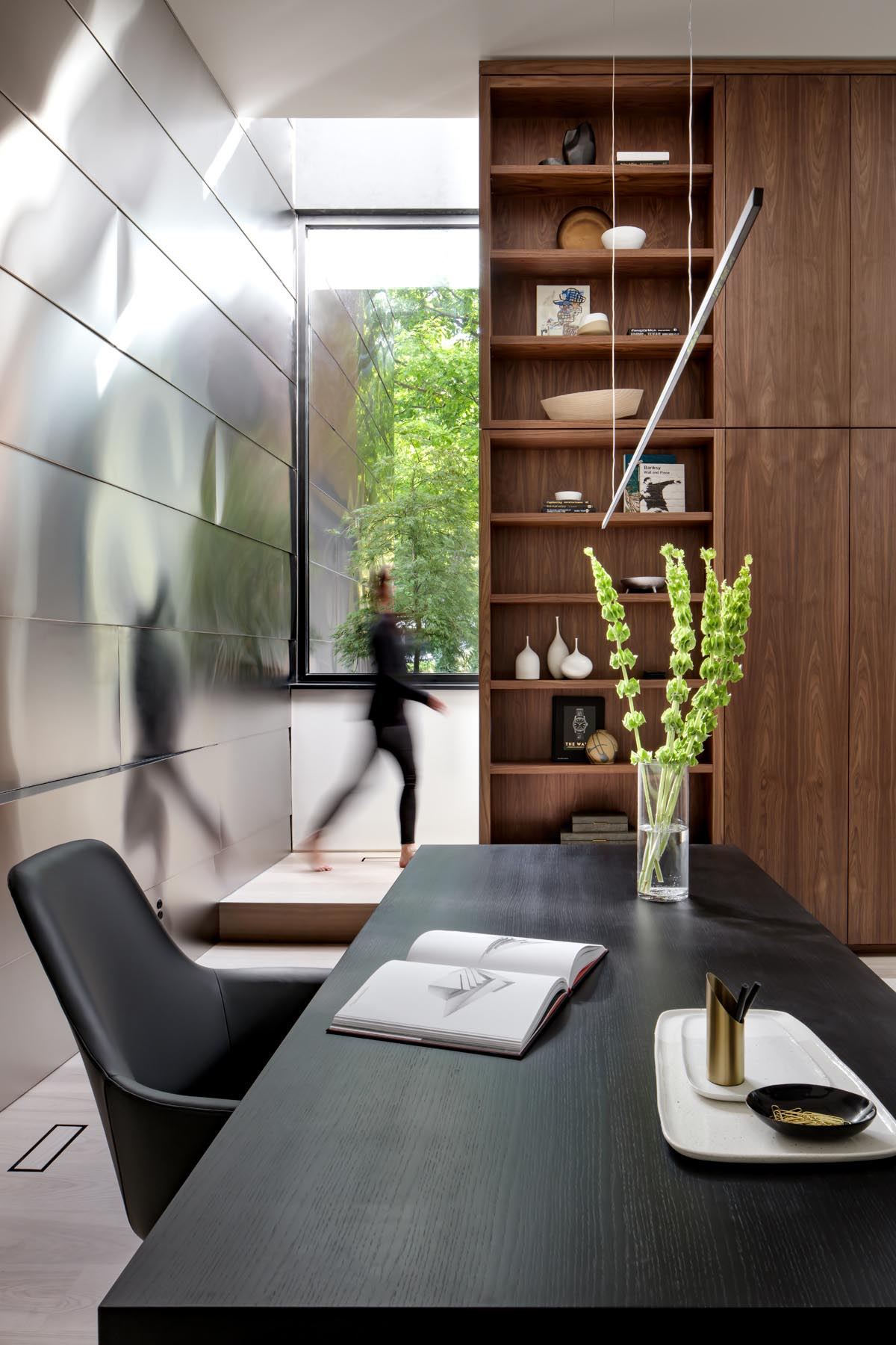 An open plan home office with walnut shelving.