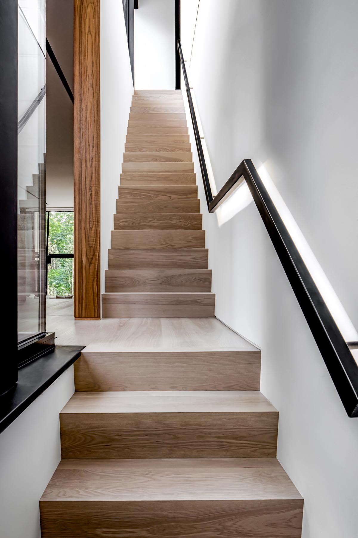 Wood stairs connect the various levels of this modern home, with a black handrail that contrasts the white wall.