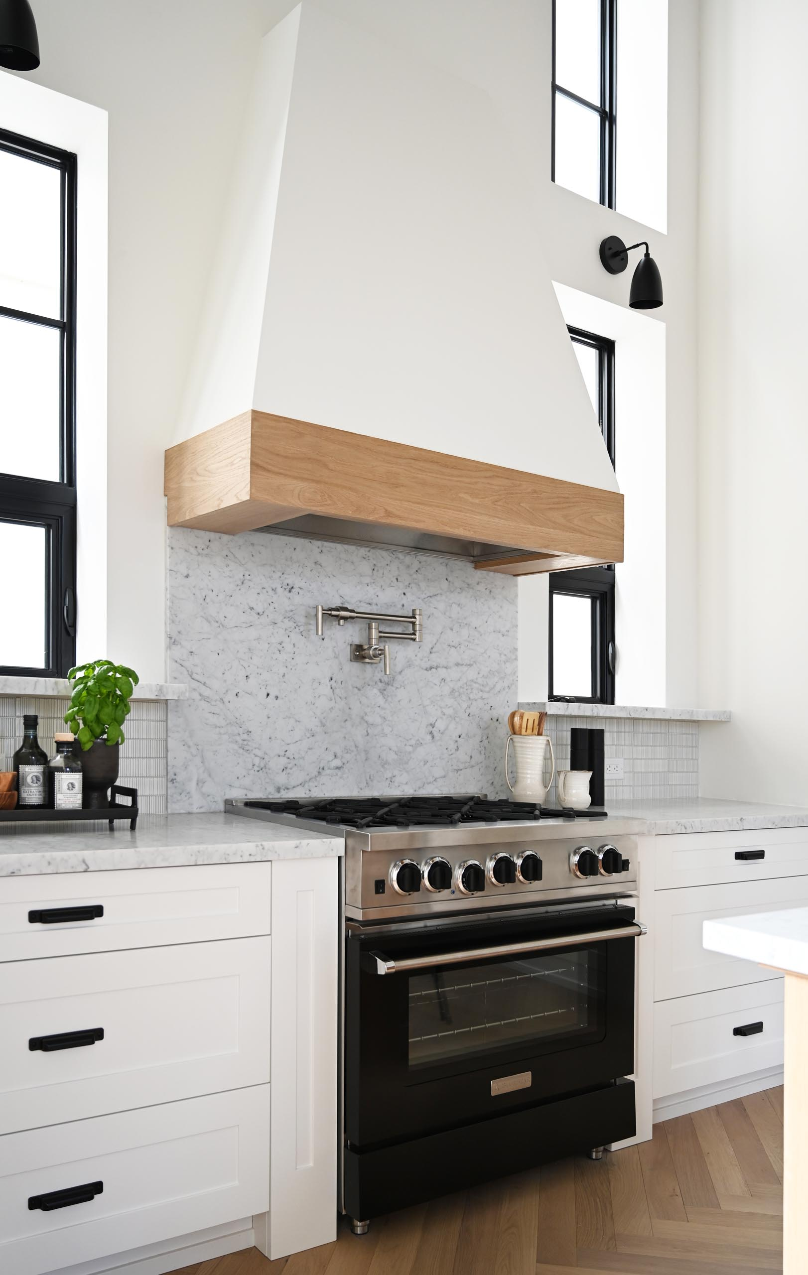 A contemporary farmhouse-inspired kitchen with gray countertops, white cabinets, and wood accents.