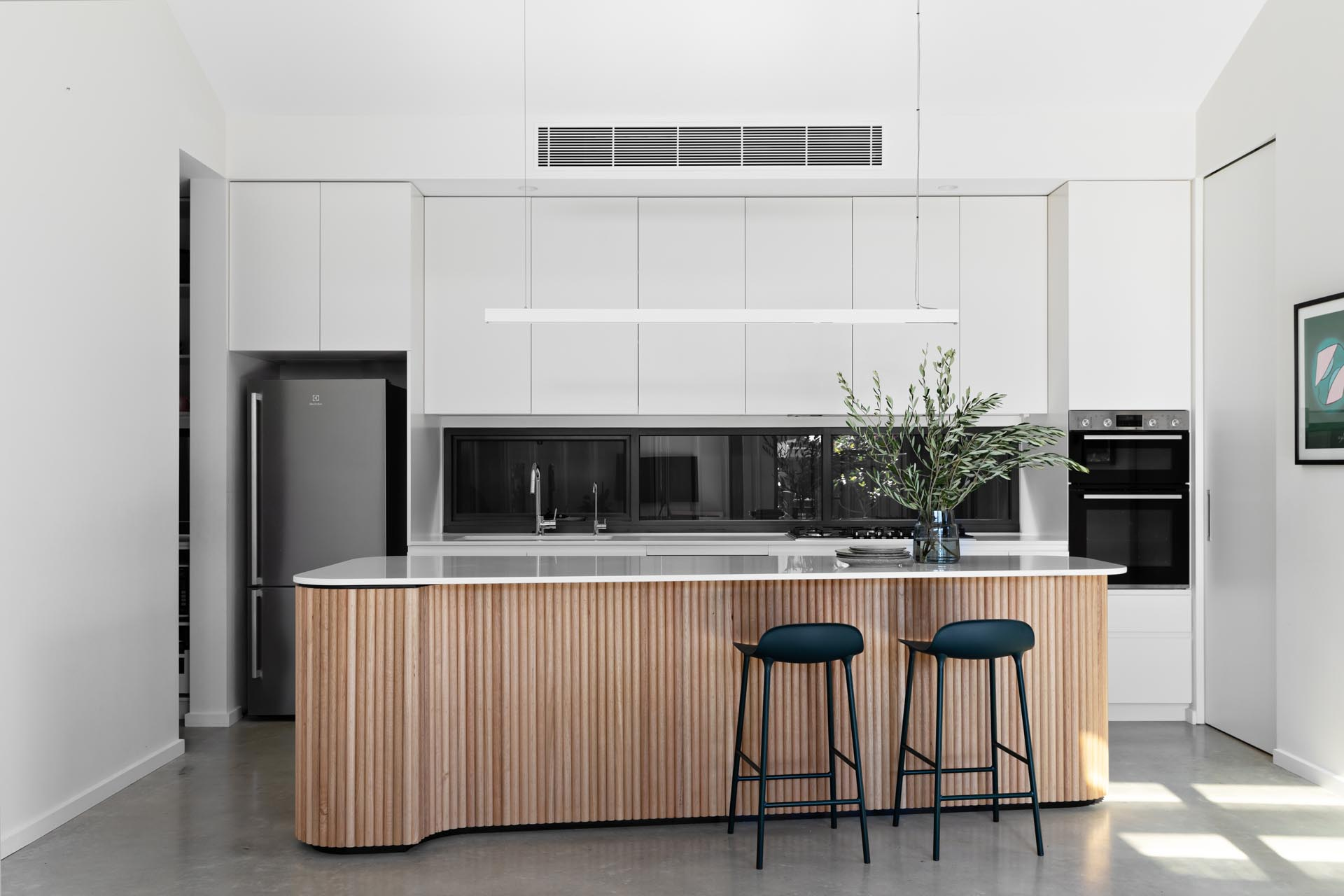 In this modern kitchen, there's minimalist white cabinets, concrete floors, a glass backsplash, and an island with wood facade.