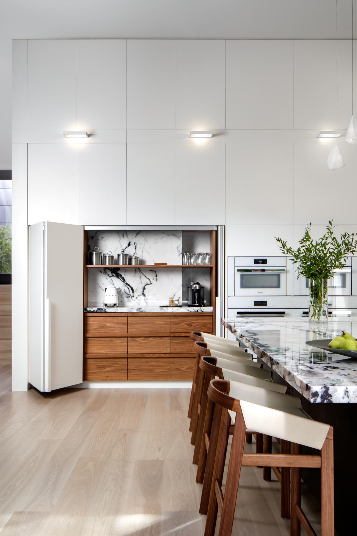 In this kitchen, minimalist white cabinets line the walls, while a large island provides space for multiple stools. Hidden within the cabinetry is a dedicated coffee station.