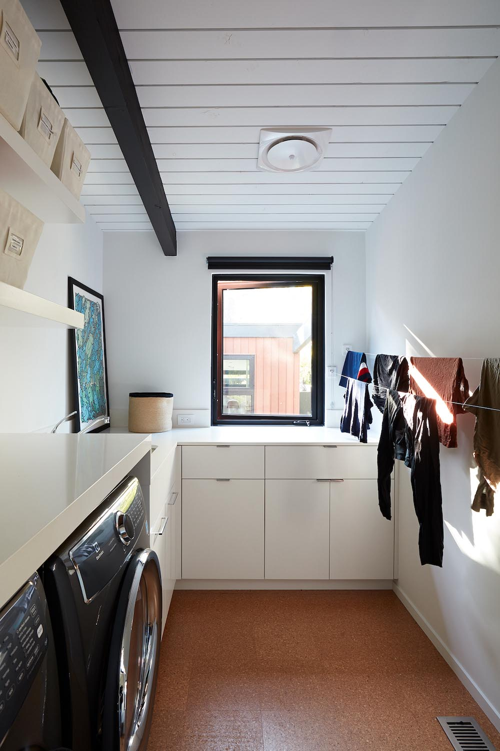 This modern laundry room includes cabinetry that wraps around the corner of the room, a countertop that continues above the washer and dryer, floating shelves, and drying lines.