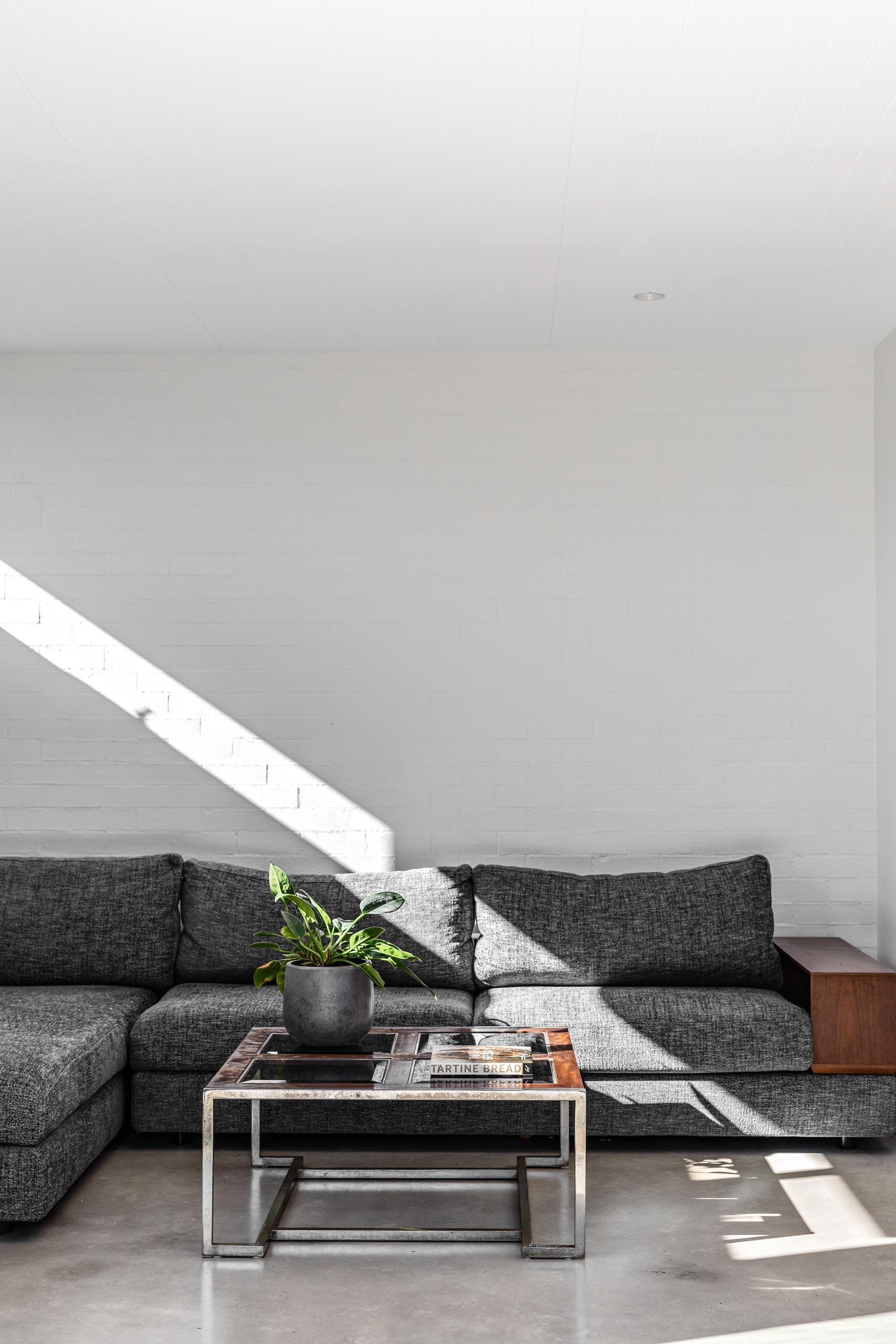 A textured white wall provides a backdrop for the gray couch with wood accents.