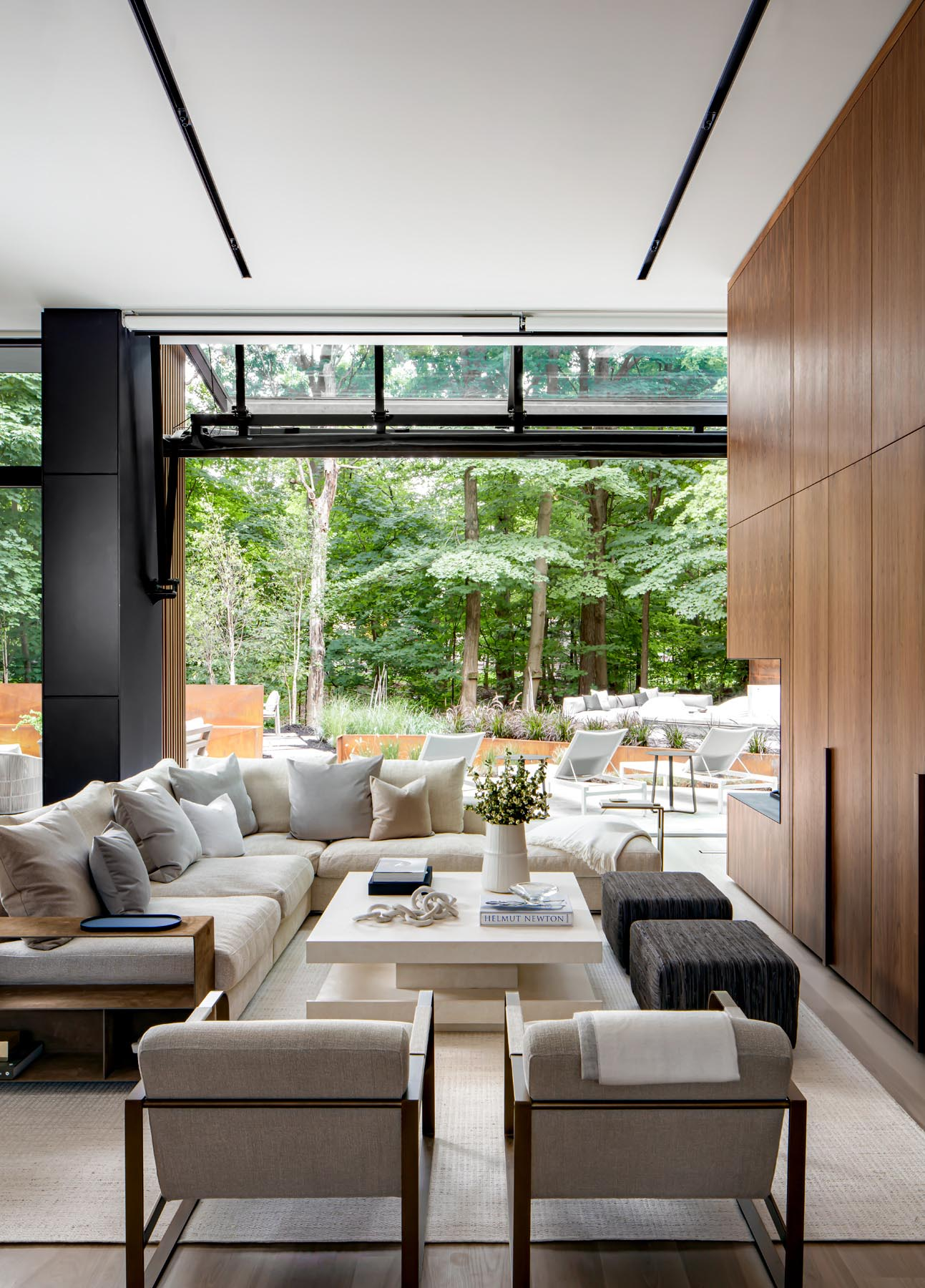 This modern living room includes a folding glass wall, two bi-fold pocket doors that open up and hide away, revealing the TV and open shelving, as well a three sided open flame custom fireplace.