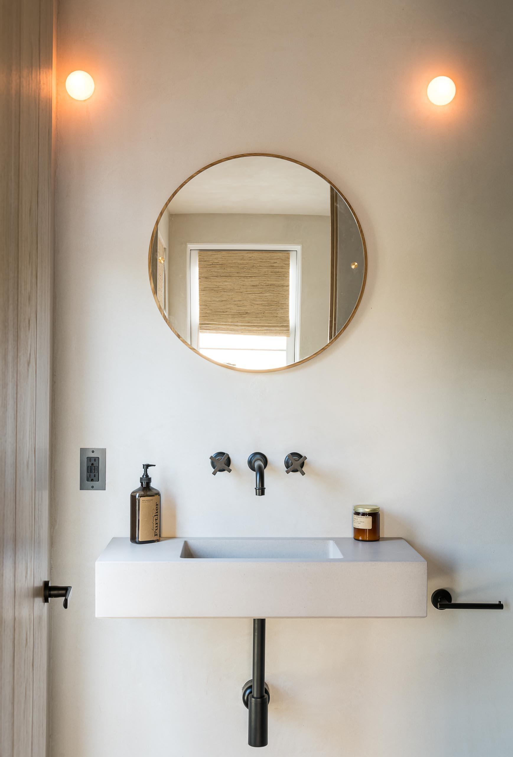 A minimalist bathroom sink with a round mirror and black hardware.