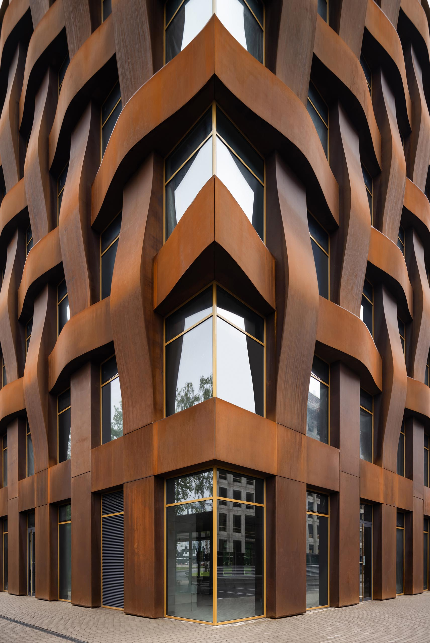 """The sculptural weathered steel facade of this modern office building is constructed in a geometric grid and presents itself as a dynamic, organically flowing fabric of loose """"warp and weft"""" threads."""