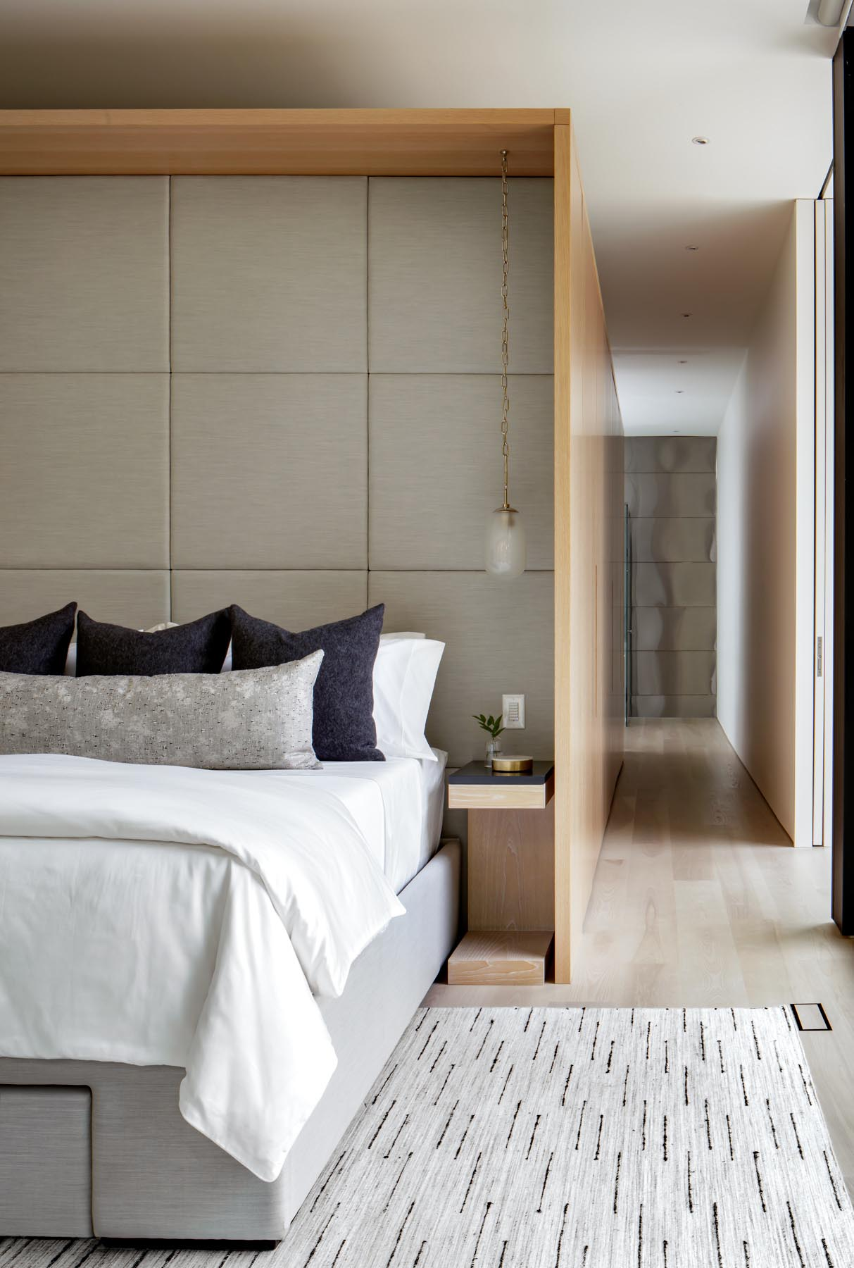 This modern primary bedroom has floor-to-ceiling windows, and a sliding glass opens to a private outdoor space.