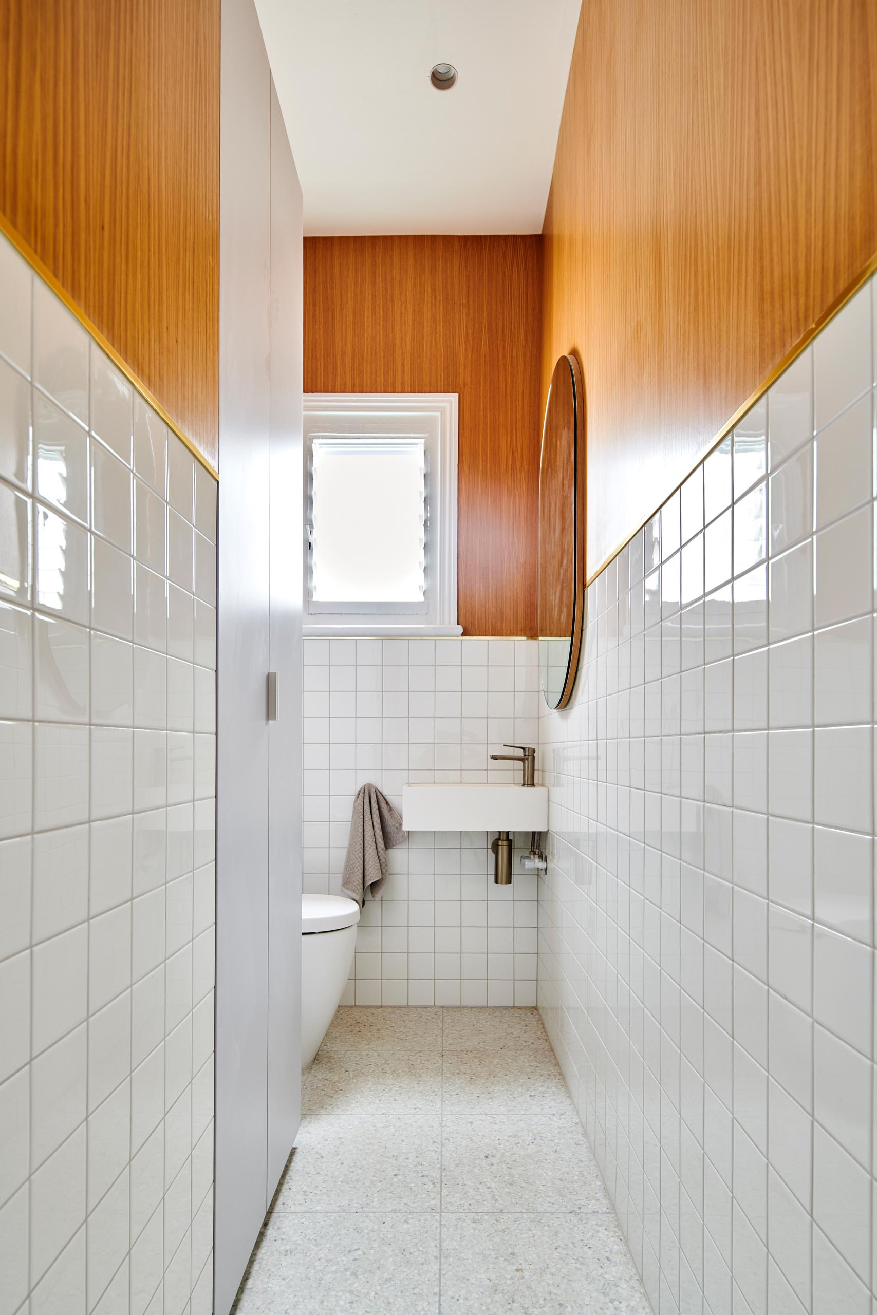 A modern white bathroom with wood accent.