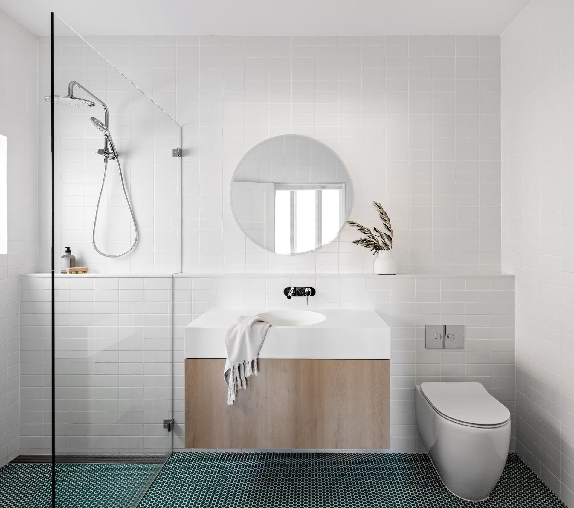 A modern bathroom with white wall tiles, white grout, a round mirror, a wood vanity with thick white countertop, and dark green penny tile flooring.