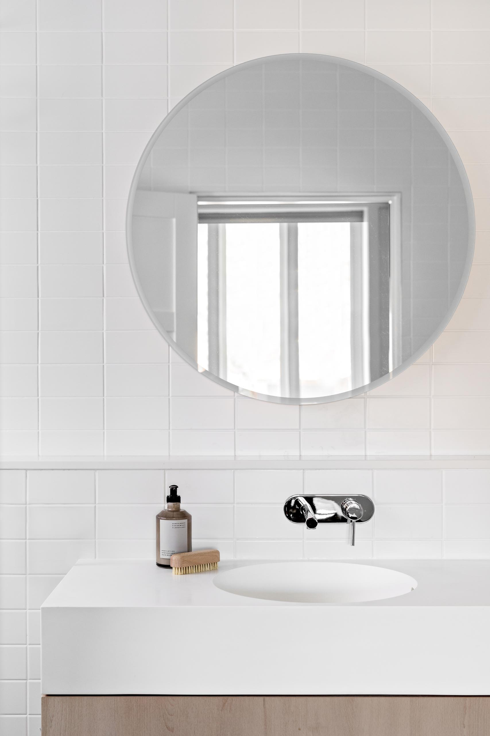 A modern white bathroom with white tiles, white grout, a round mirror, and wood vanity with thick white countertop.