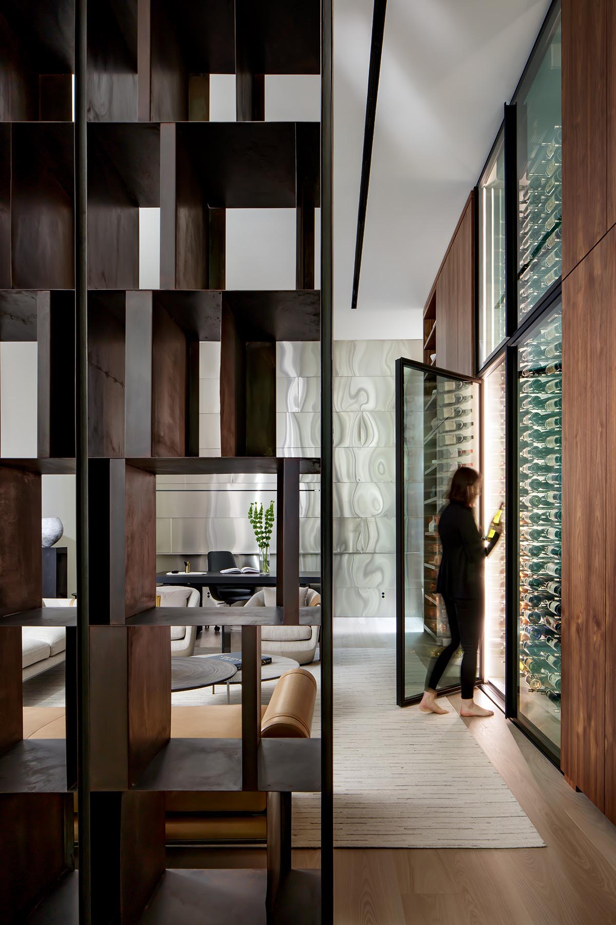 A walnut accent wall showcases a pair of floor-to-ceiling, temperature controlled wine fridges,