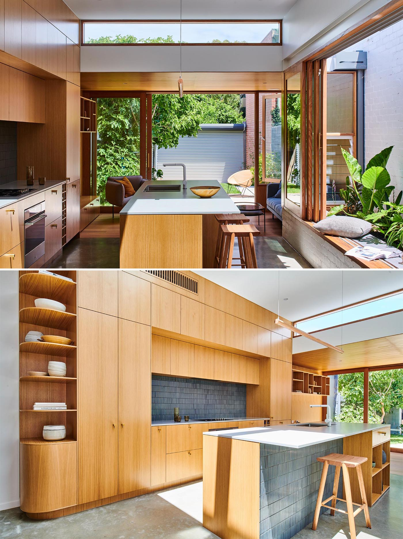 A modern wood kitchen with a large window open to a small garden, gray tiles, an island, open shelving, white countertop, and built-in wine storage.