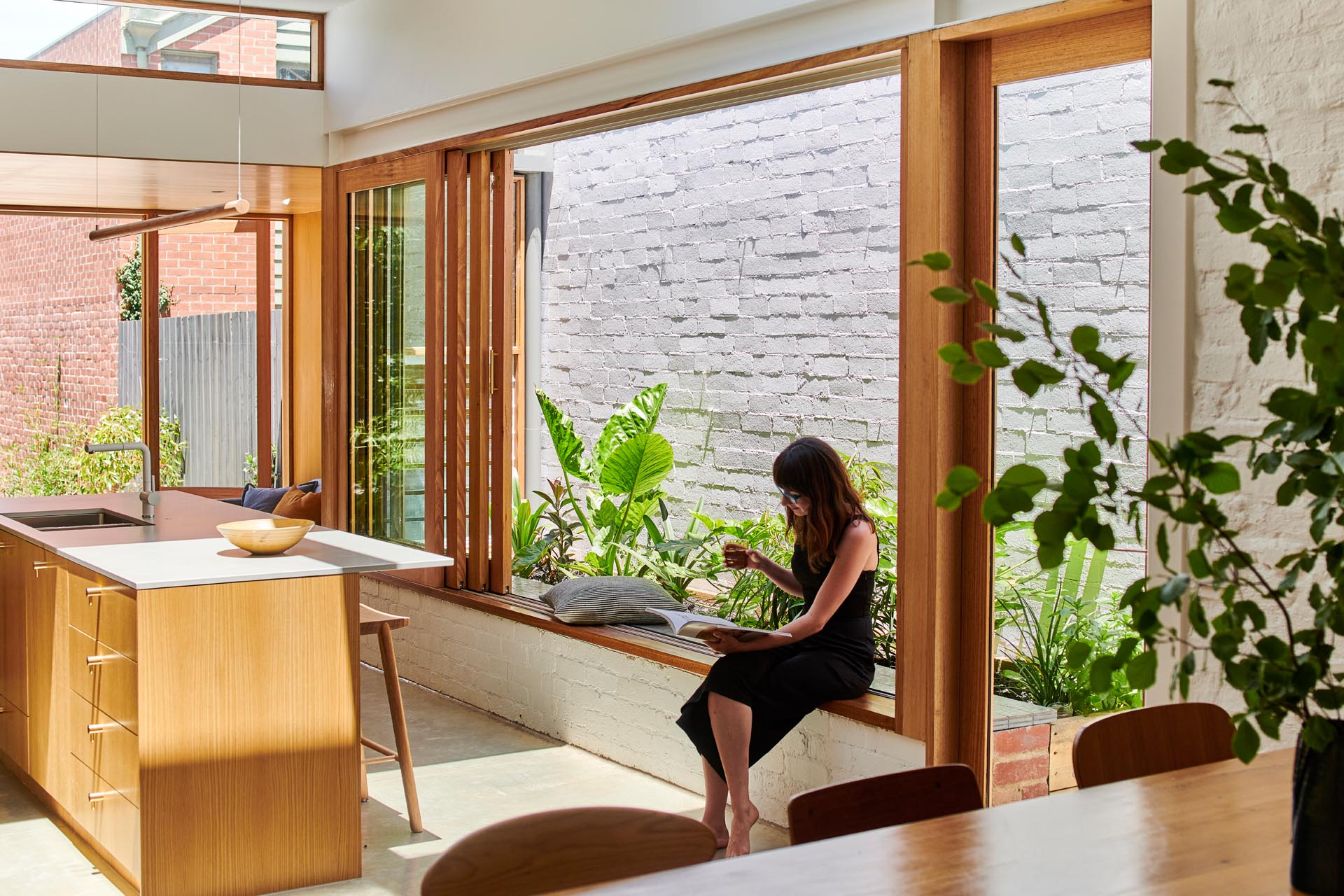 A window frame that doubles as a window seat, allowing the kitchen to become a gathering space for both family and friends.