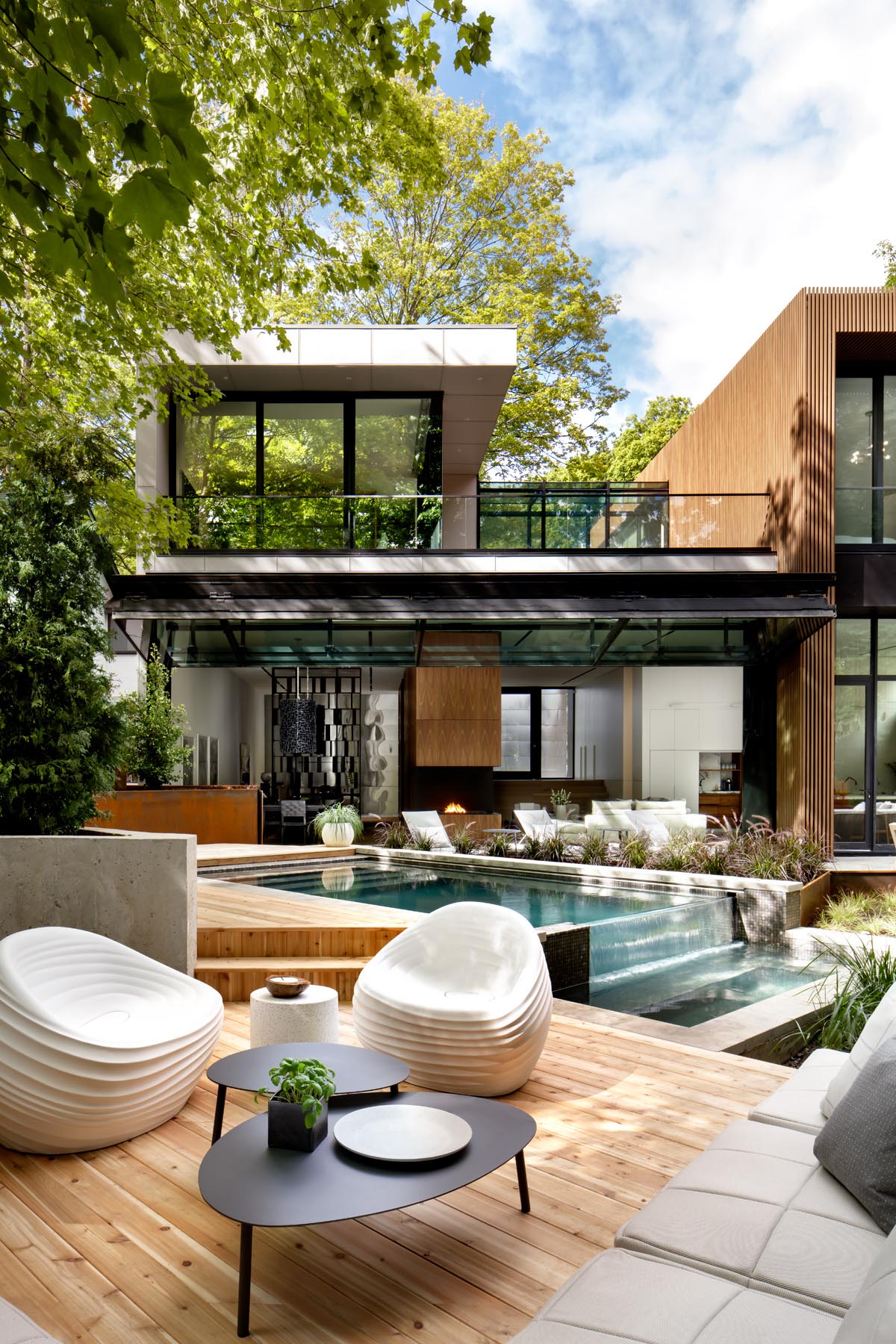 This modern outdoor space has been landscaped with a variety of different areas, including a swimming pool and deck, a lounge area with outdoor kitchen and fireplace, and a dining area.