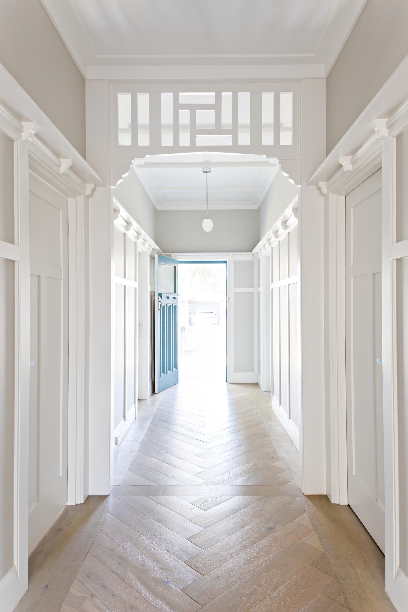A renovated hallway with herringbone wood flooring.