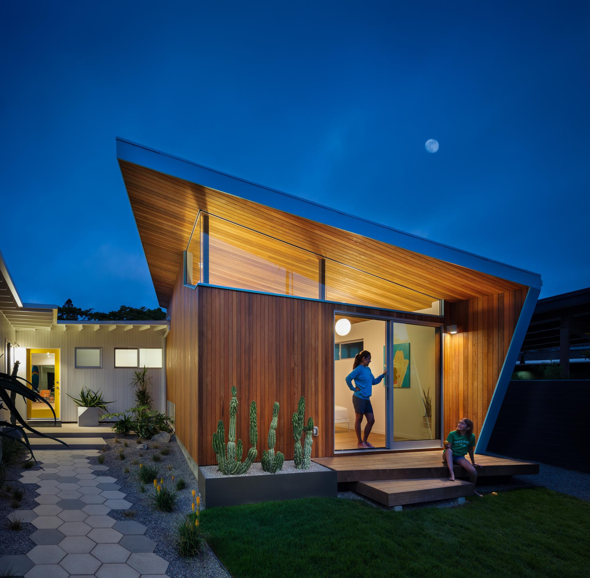 The updated exterior of this mid-century modern home showcases more usable green space and a permeable grass driveway, while an all new pavilion stands out by the tall-angled roofline with blue accents, and hexagonal pavers lead to the yellow front door.