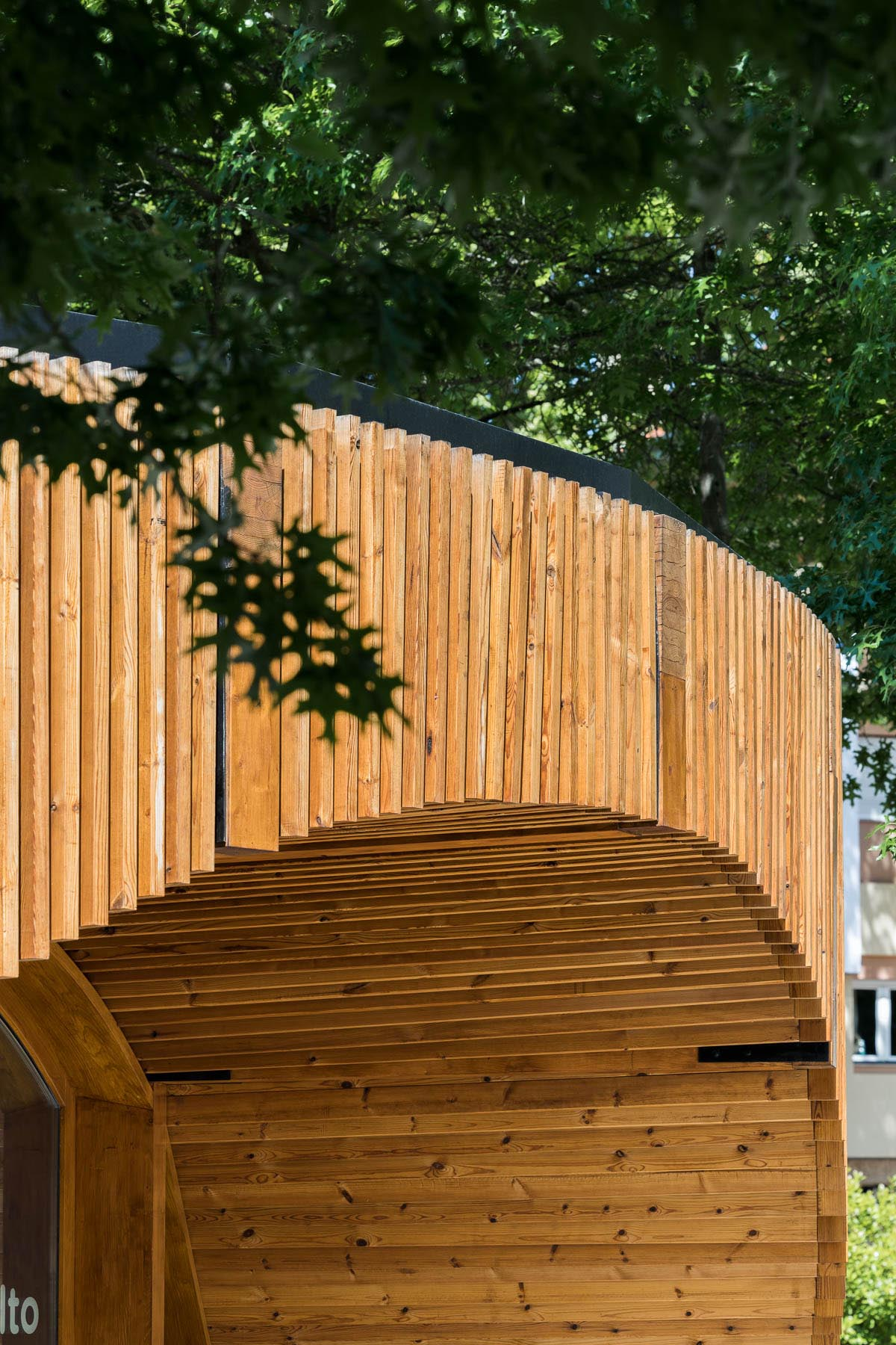 A small modern building has a circular design that's covered in vertical wood slats.