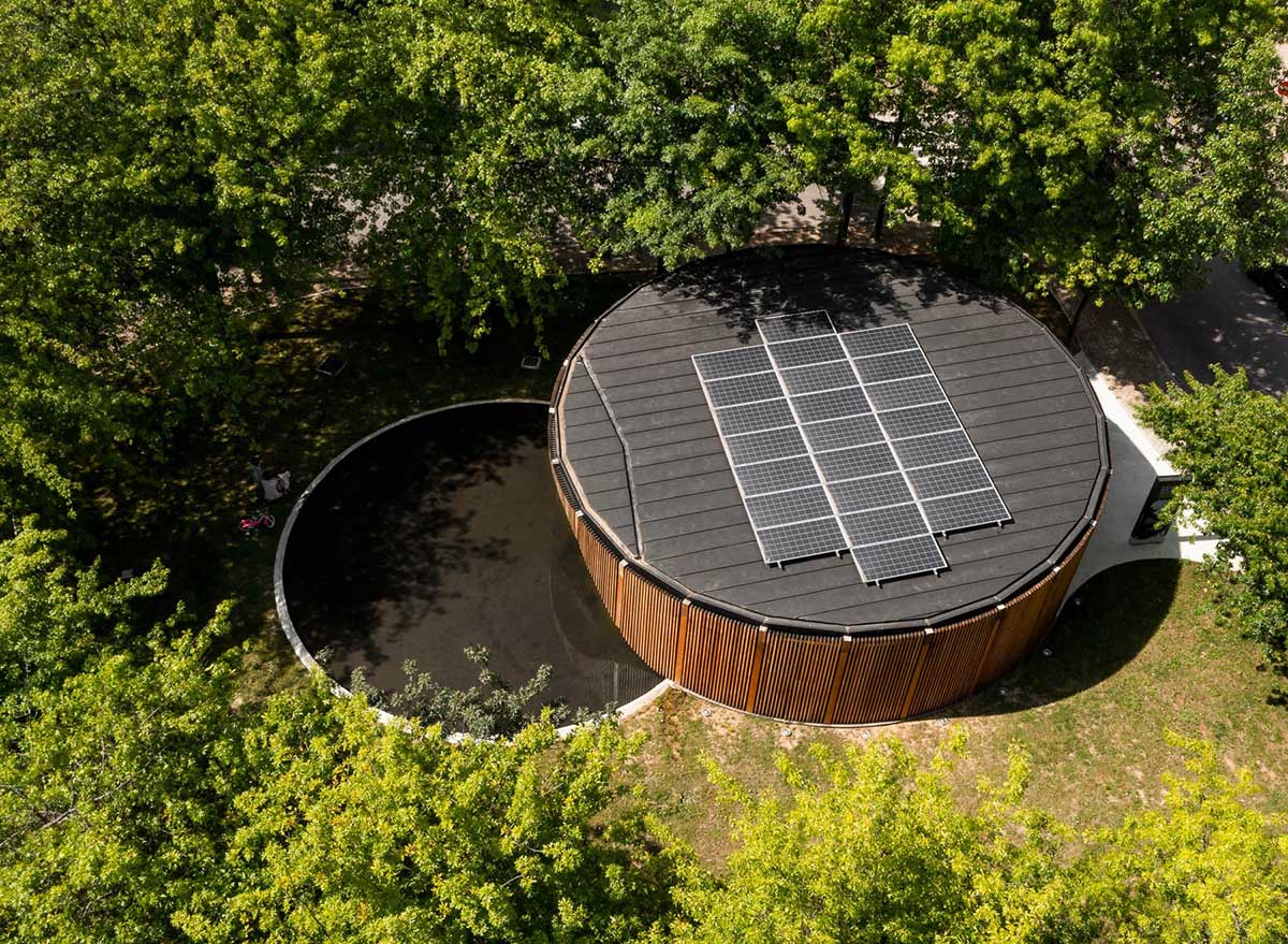 The circular design of this modern building is accented by a curved water feature as well as solar panels on the roof.