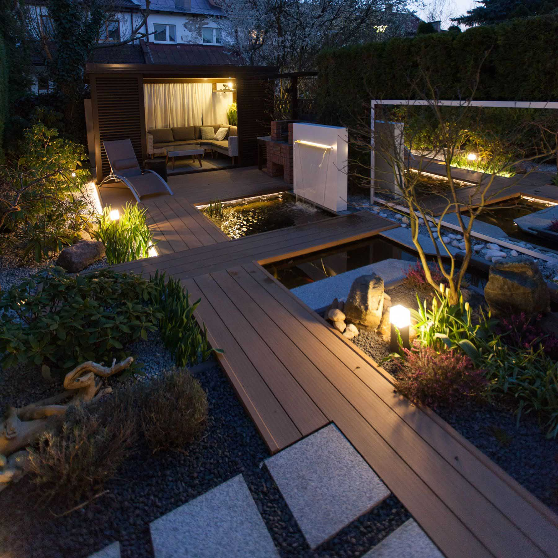 A modern backyard with wood pathways, water features, and a small covered living space.
