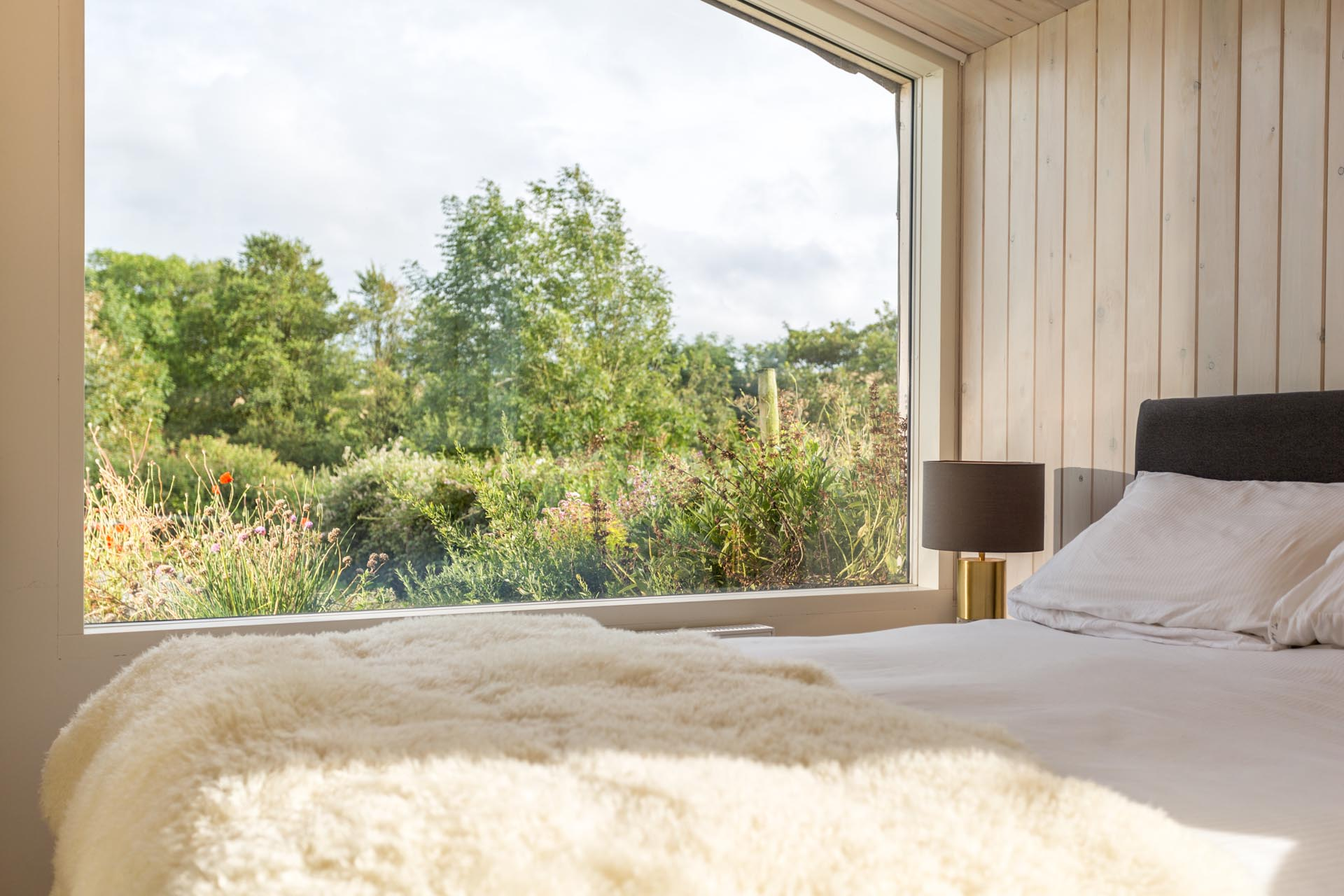 In this modern bedroom, there's wood walls and ceiling, and a large picture window perfectly frames the garden views.