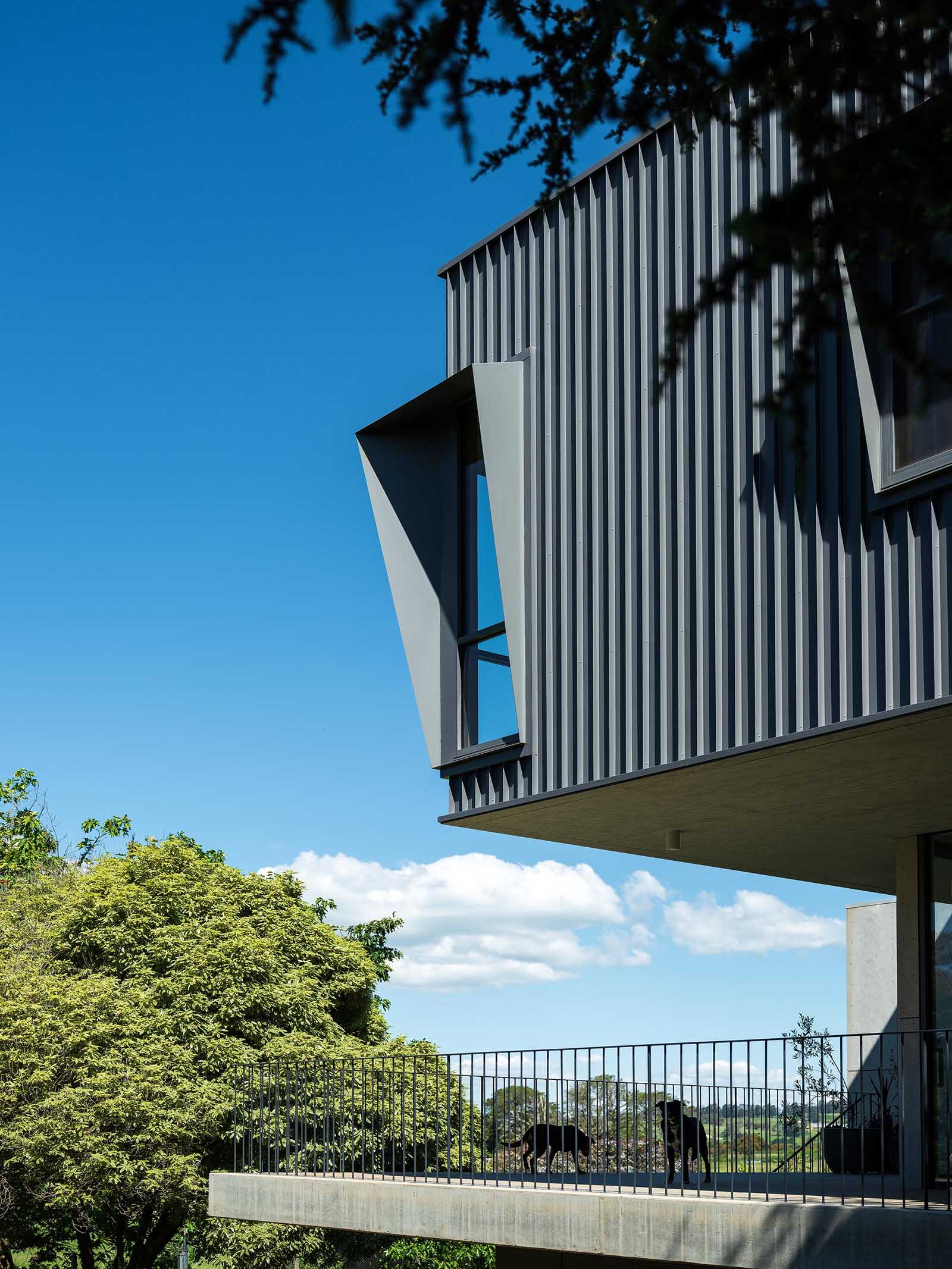 The modern black metal exterior of this home has angled window frames that protrude away from the windows, blocking the sun and offering a shaded interior.
