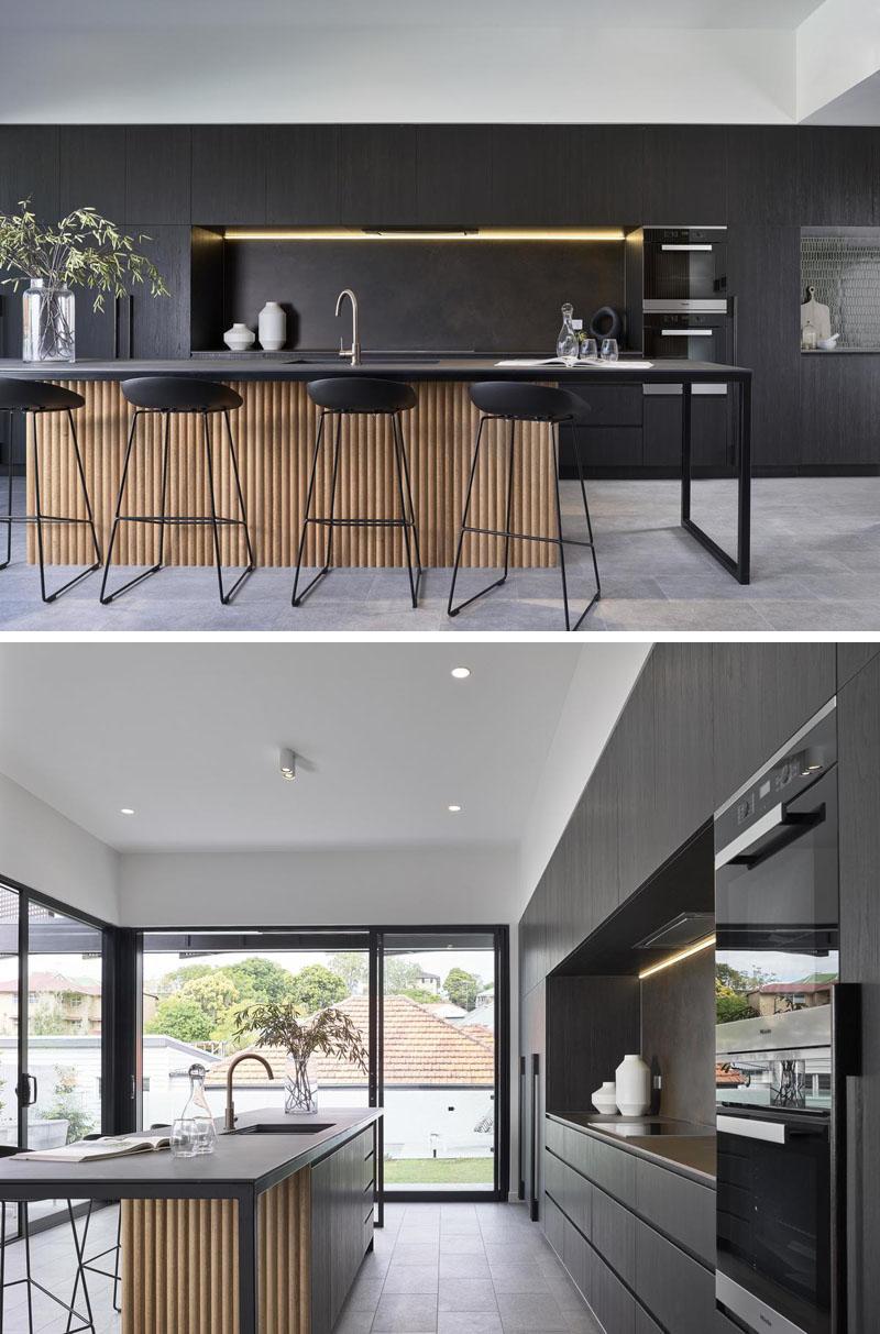 Joe Adsett Architects has designed a modern house in Brisbane, Australia, with black kitchen cabinets.
