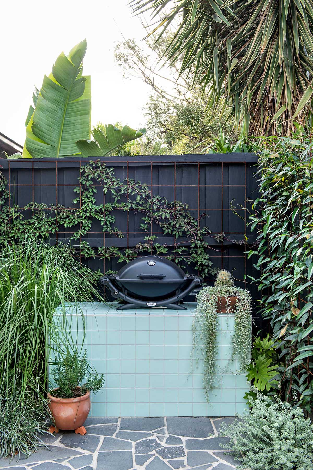 A small bbq area with a mint green tiled outdoor workspace.