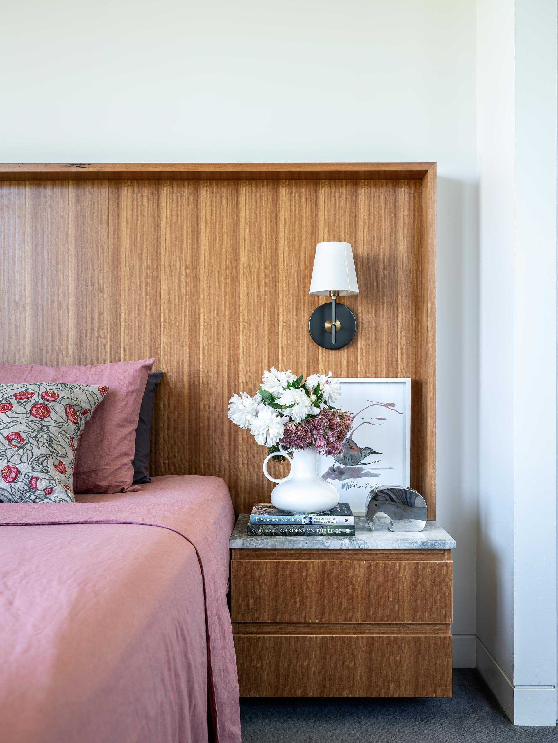 In this modern bedroom, a wide wood headboard incorporates a floating bedside table.