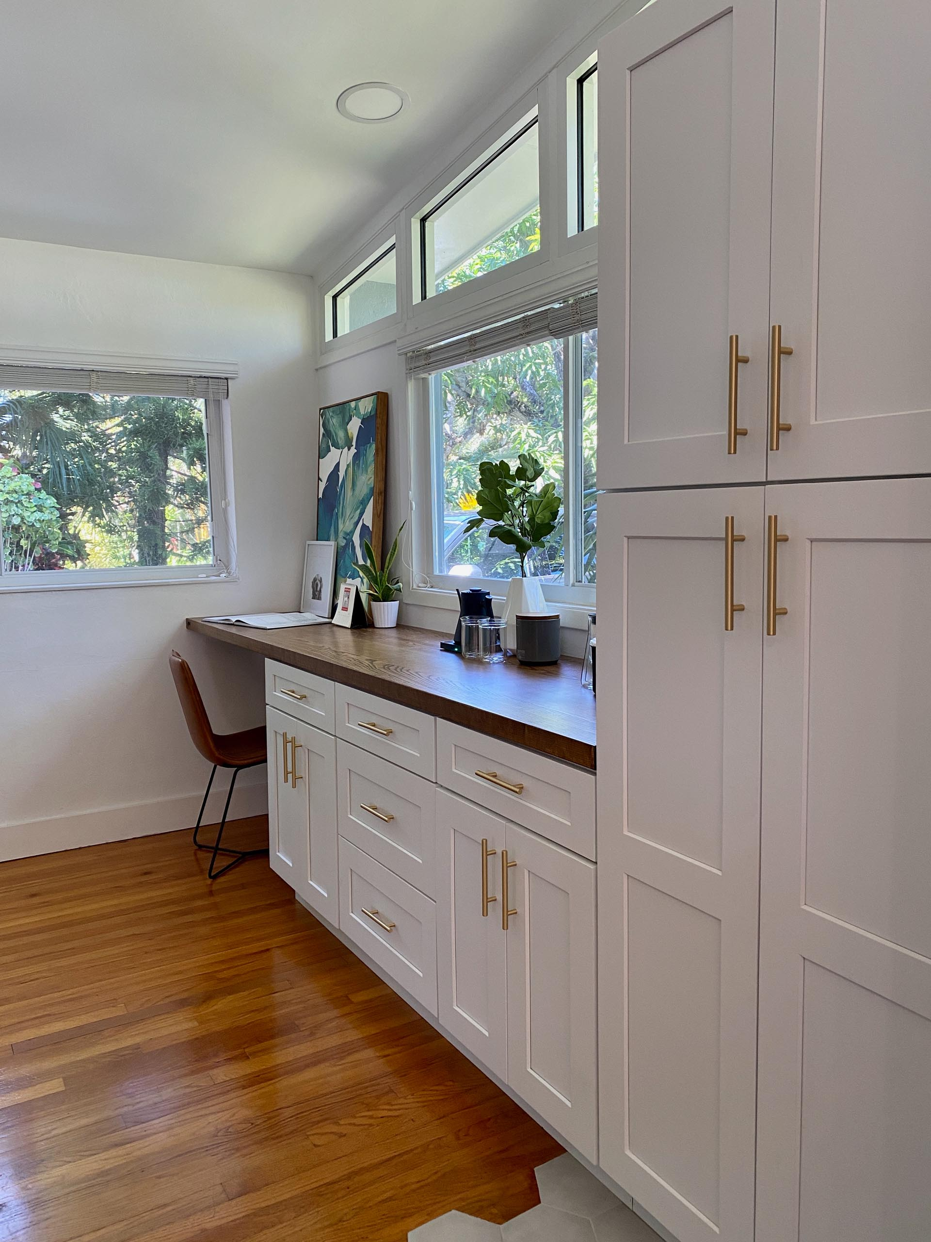 The kitchen cabinets continue along the wall and a wood countertop has been introduced to create a home office and coffee station.