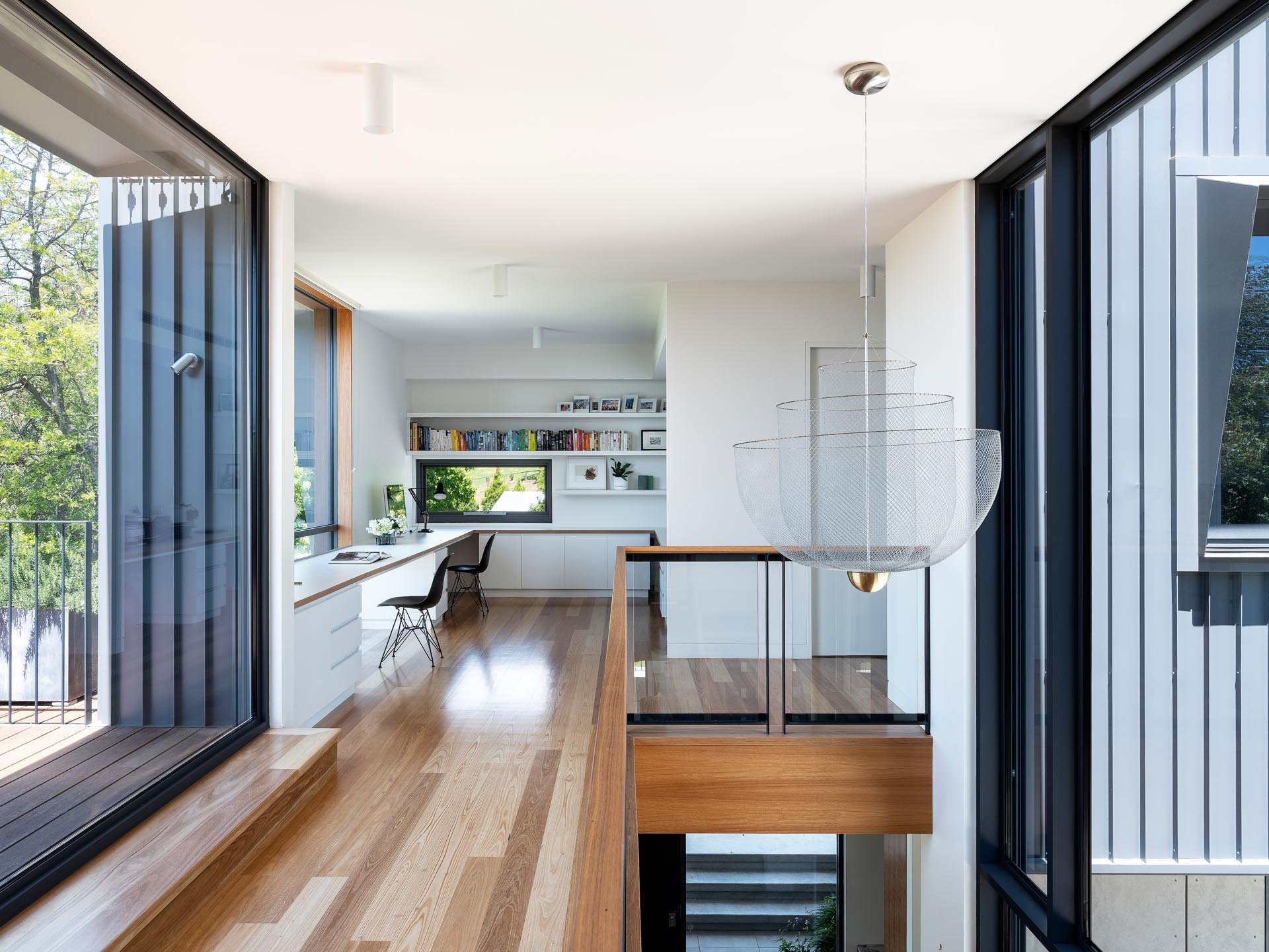 At the top of the stairs in this modern home, is a custom-designed office space that has white shelving, a long desk for two, and plenty of storage.