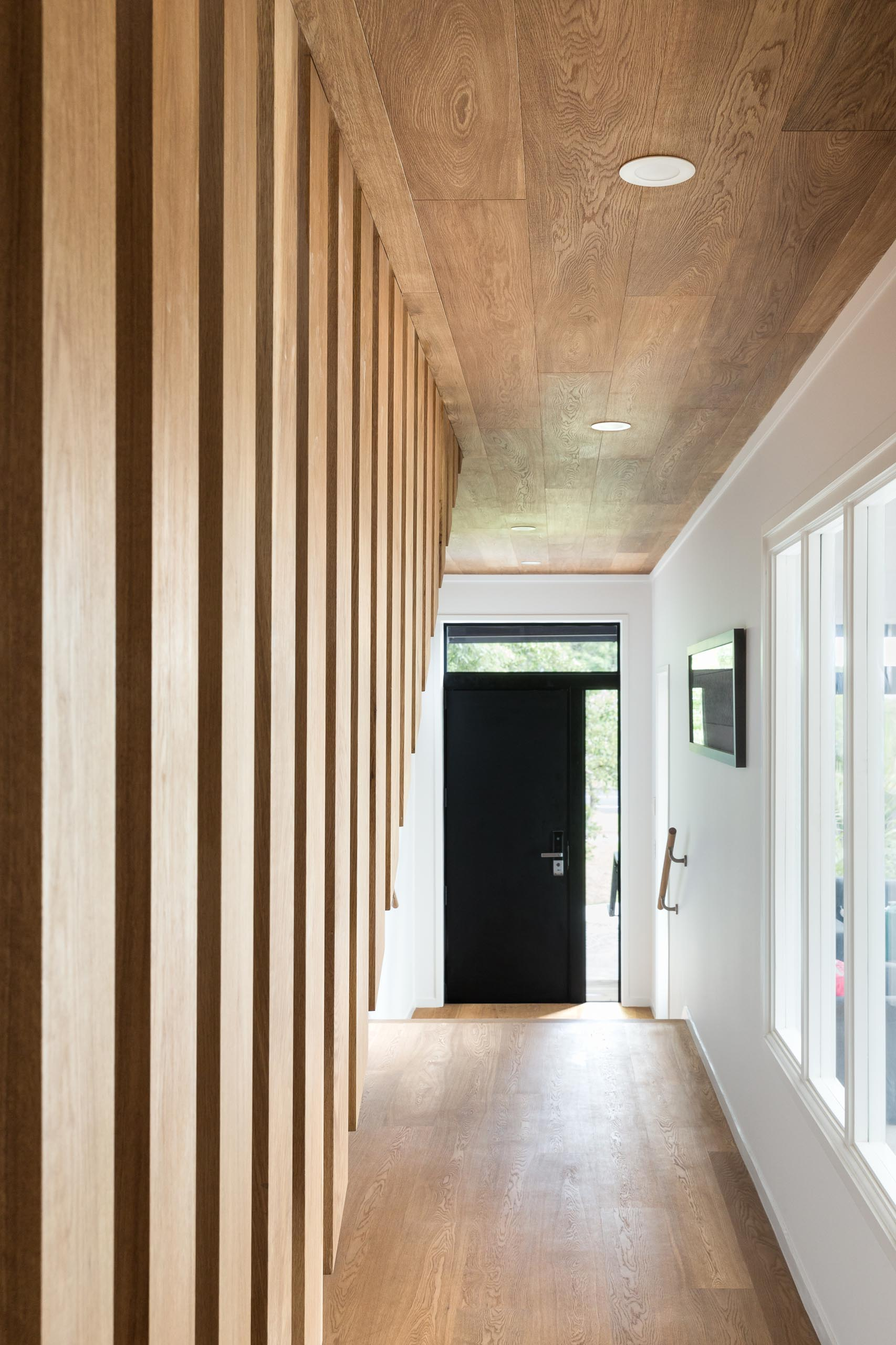 The front door opens to the entryway and hallway that has a ceiling lined with oak, adding warmth to the interior.