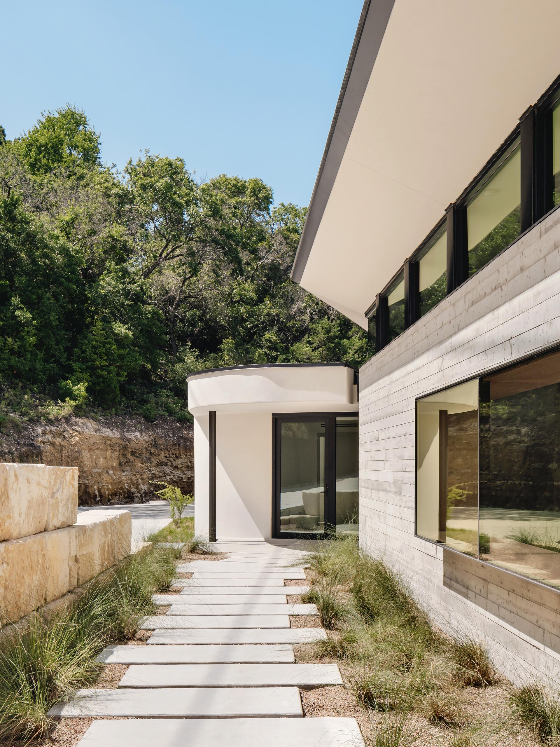 A path lined with grasses runs alongside this modern house and its board formed concrete wall, and guides people to the entryway with a wood accent wall.