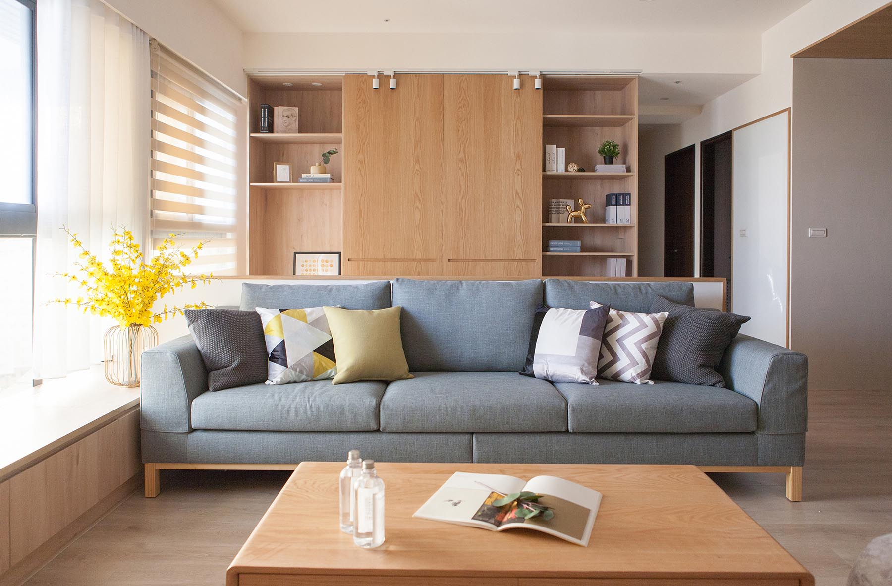 A contemporary living room with a light gray couch and wood shelving.