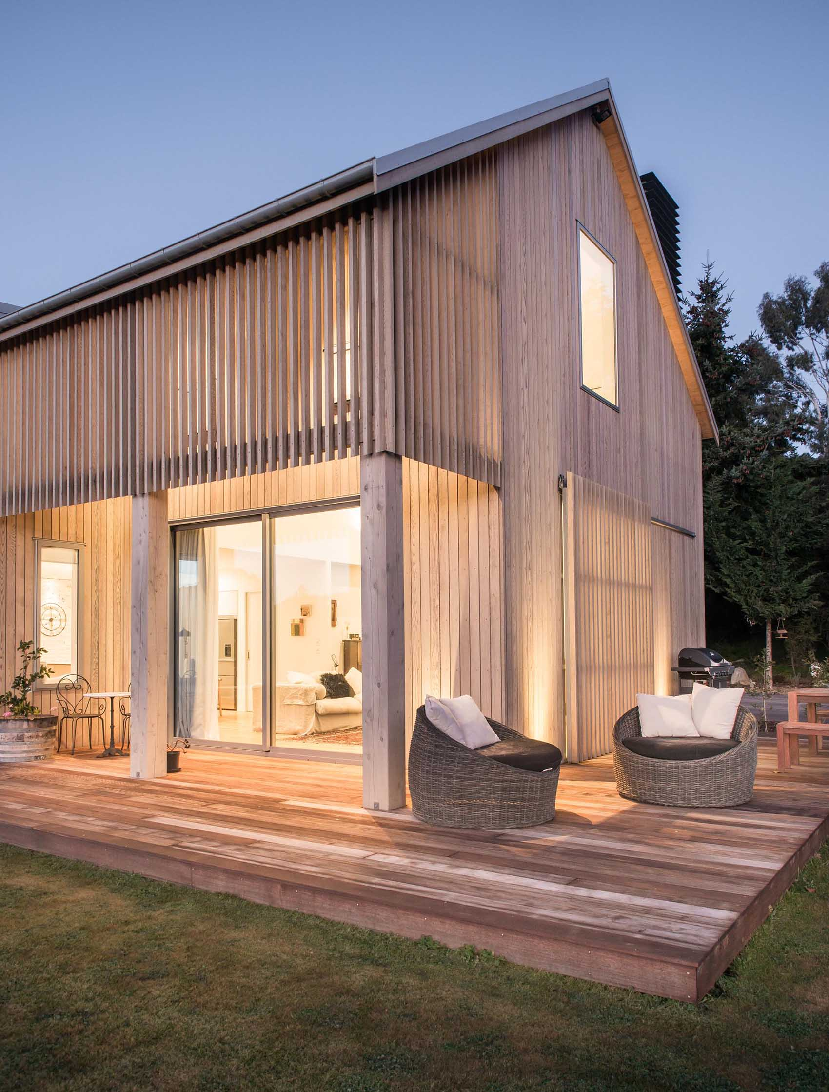 A contemporary barn-inspired home  with wood cladding and a wrap around deck.