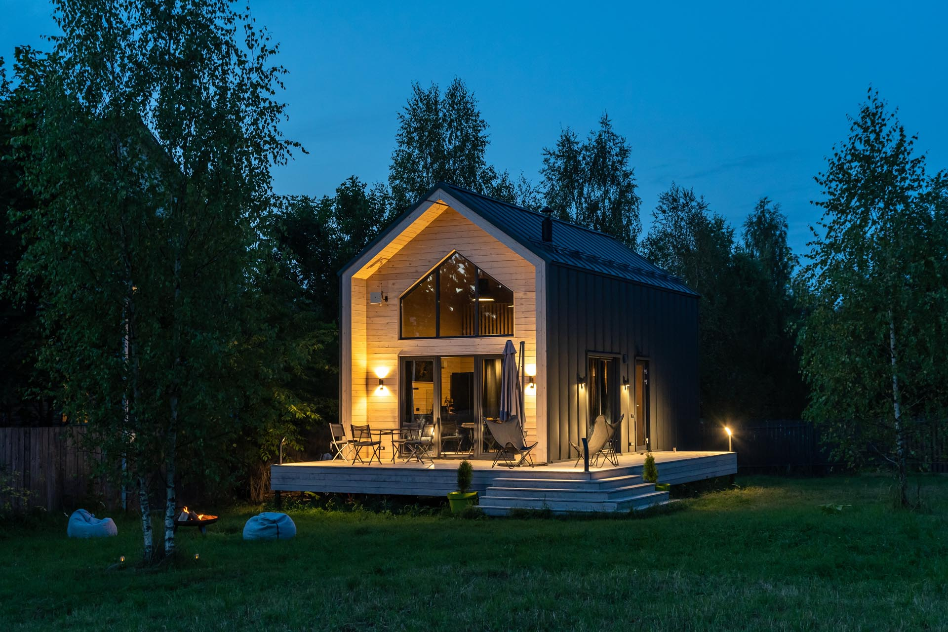 A modern barn-inspired home with a black metal exterior that's accented at each end with tongue and groove wood siding.
