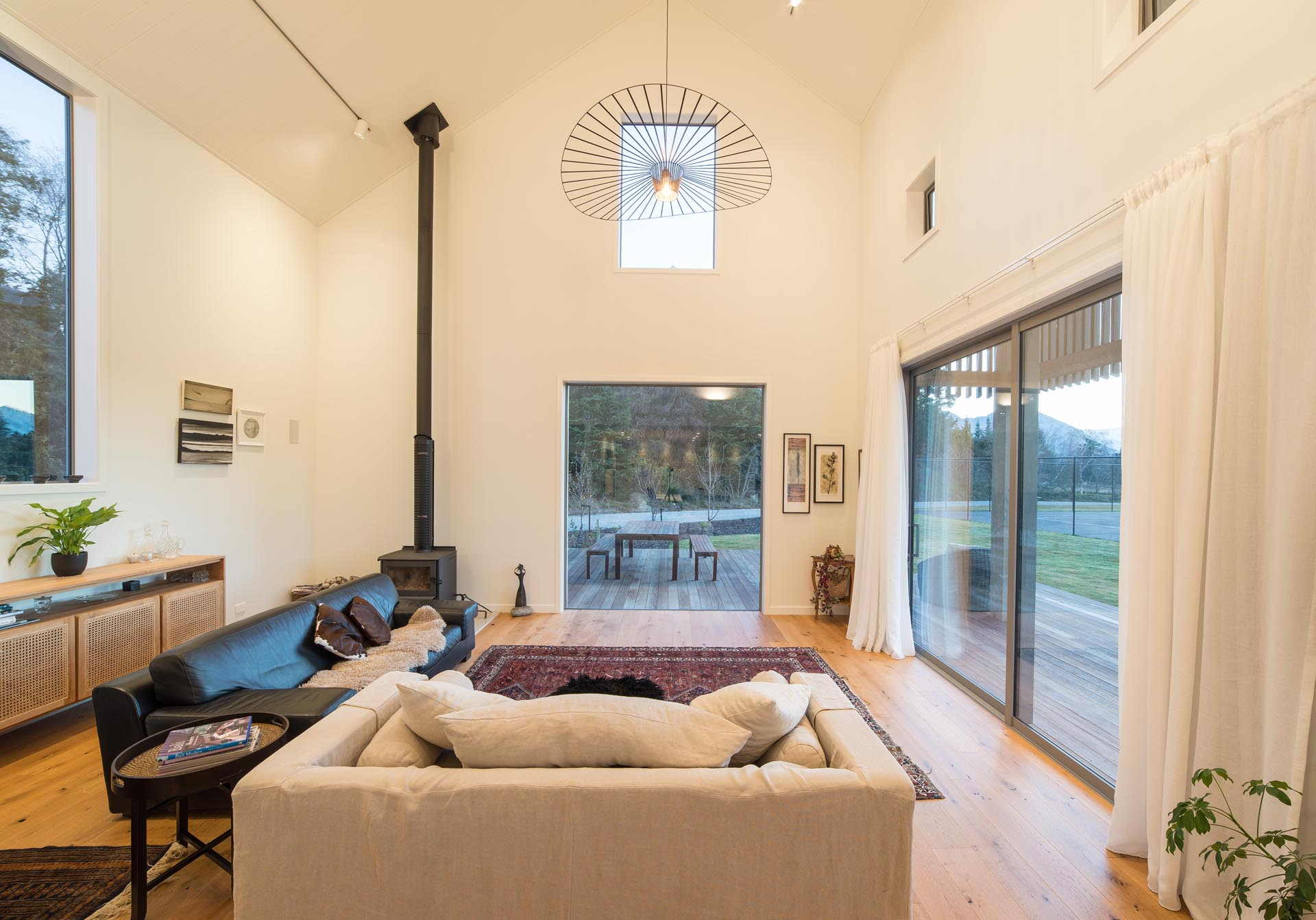 Inside this modern barn-inspired home, the living room has a sense of openness from the double height ceiling, as well as the doors that open to the wood deck outside.