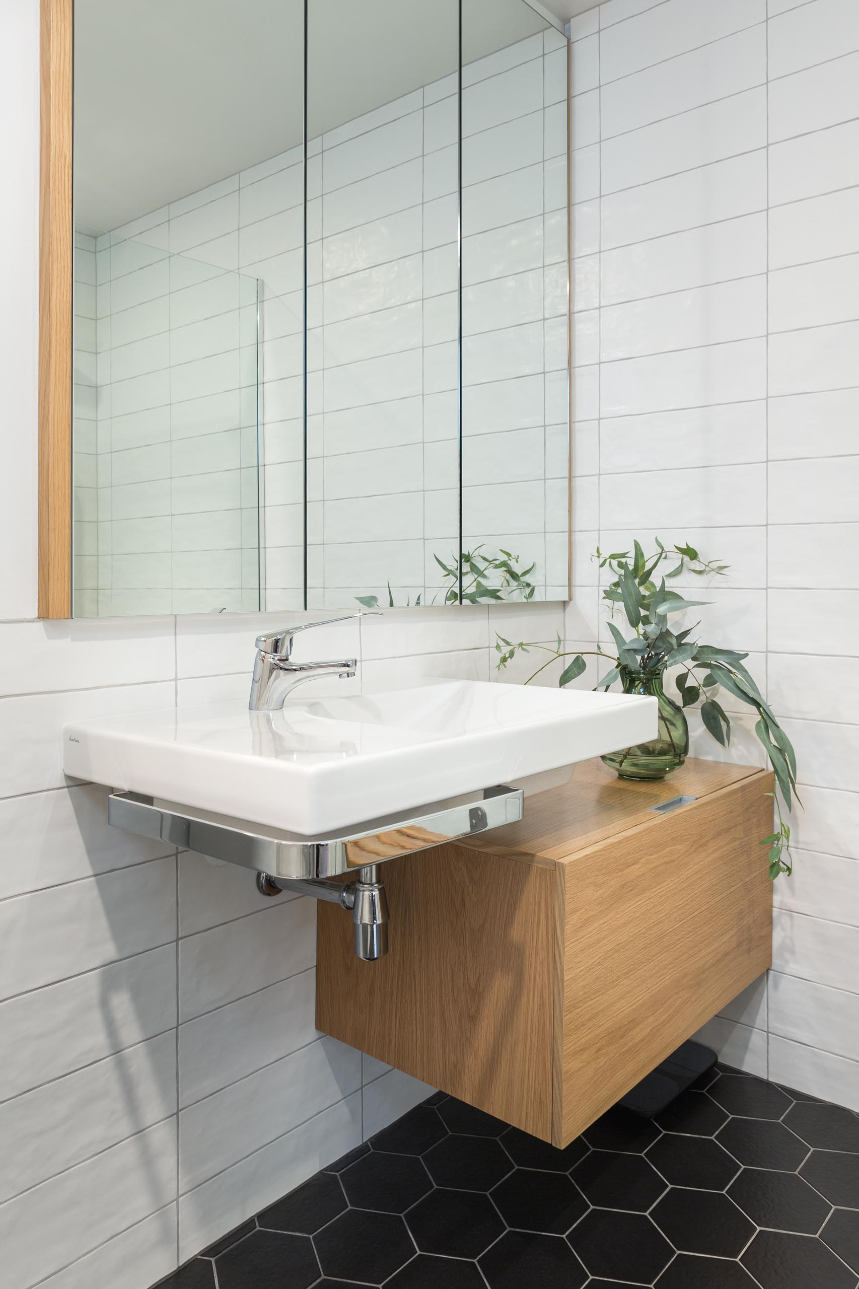 In this modern bathroom, there's black hexagon tiles on the floor and white rectangular tiles on the walls.