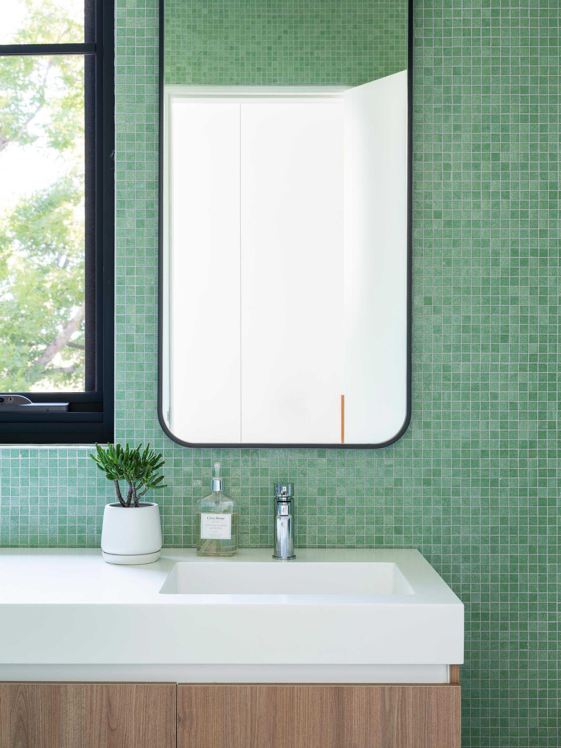 In this modern bathroom, small square green tiles cover the walls, while the black-framed mirror matches the window frame, and the white countertop with integrated sink rests atop a wood vanity.
