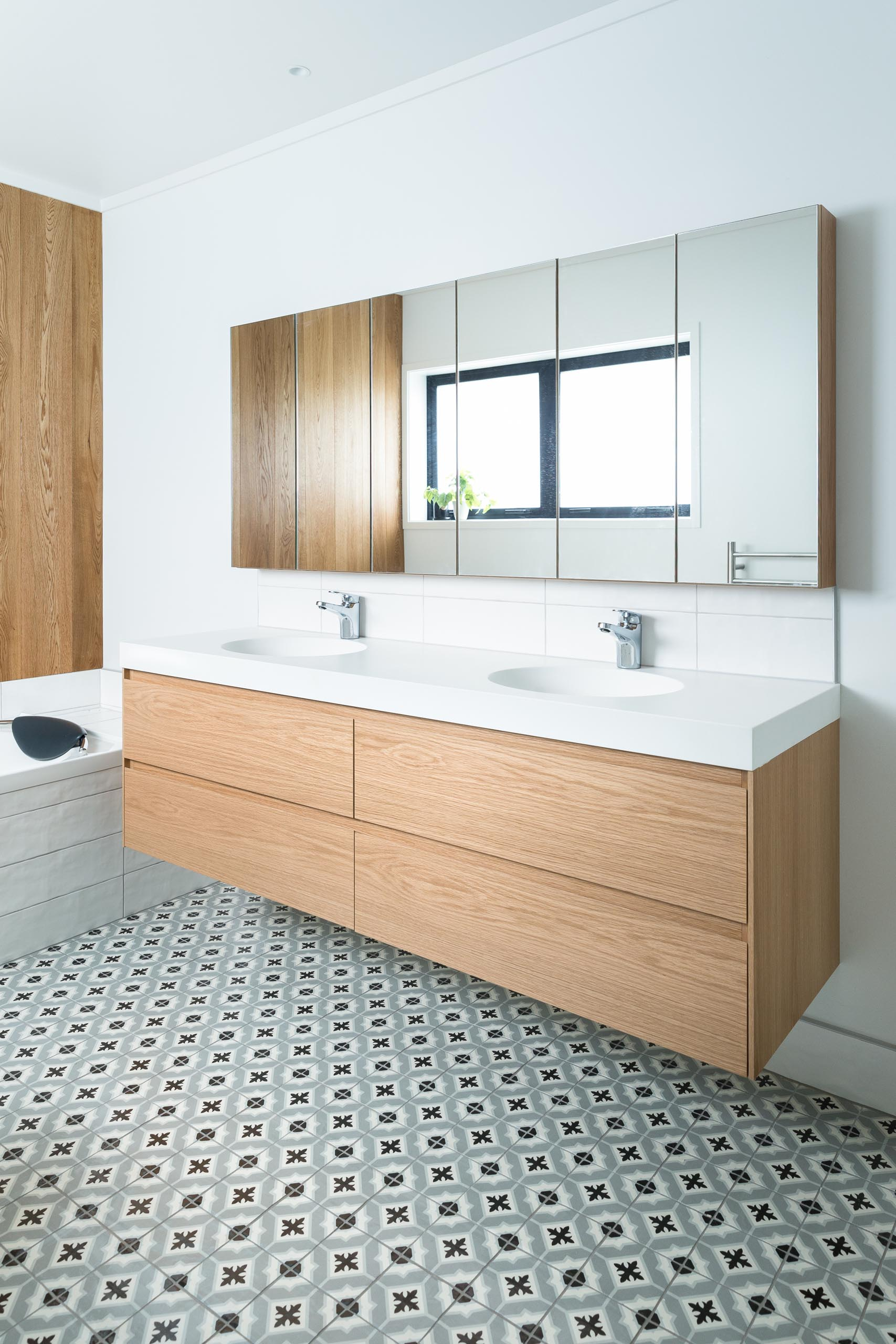 This modern bathroom features a double sink wood vanity, patterned tile flooring, a built-in bathtub, and a wood accent wall.