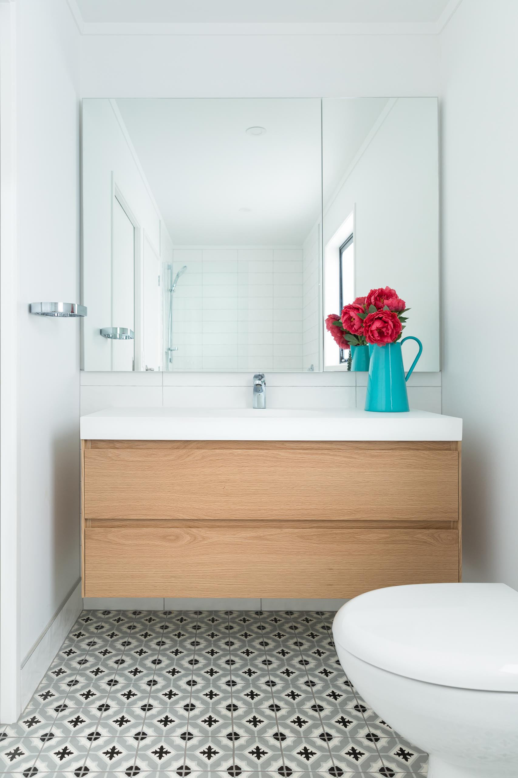 This modern bathroom includes patterned floor tiles, a floating wood vanity, a large mirror, and white wall tiles.